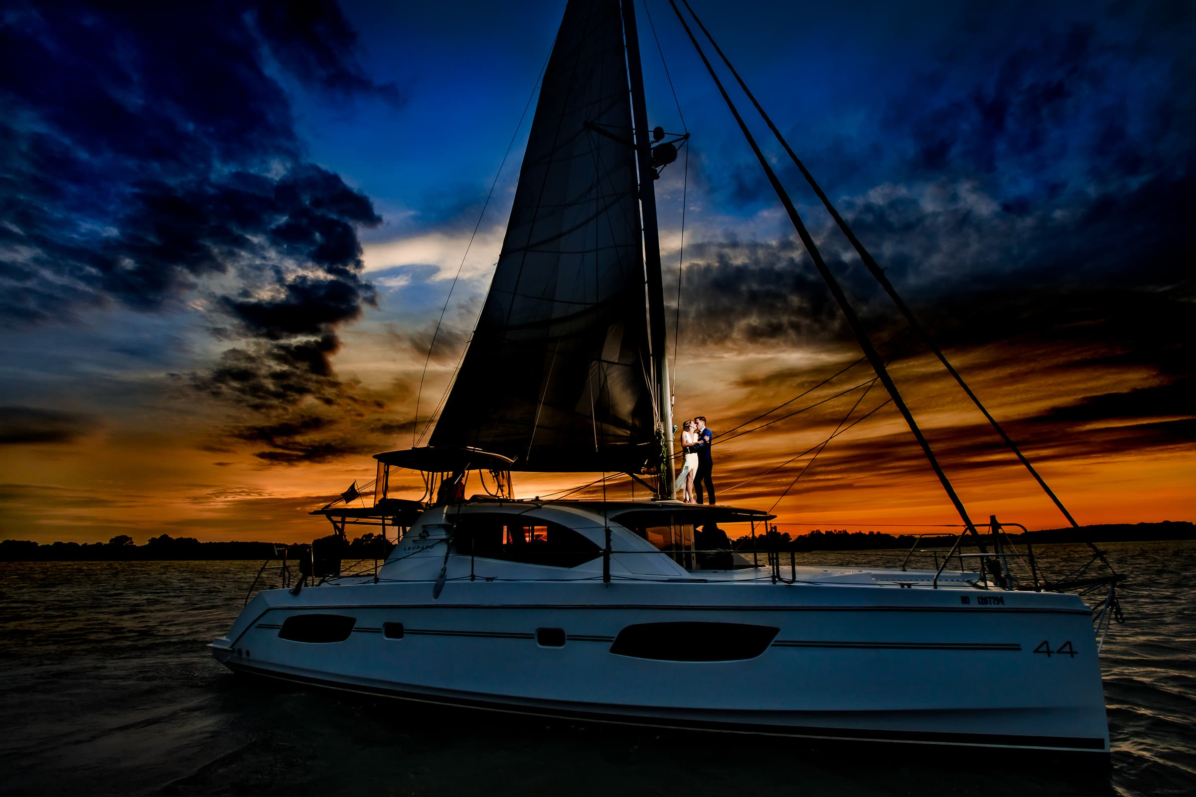 Bride and Groom beautifully lit up at sunset on their catamaran sailboat for their Chesapeake Bay Wedding.