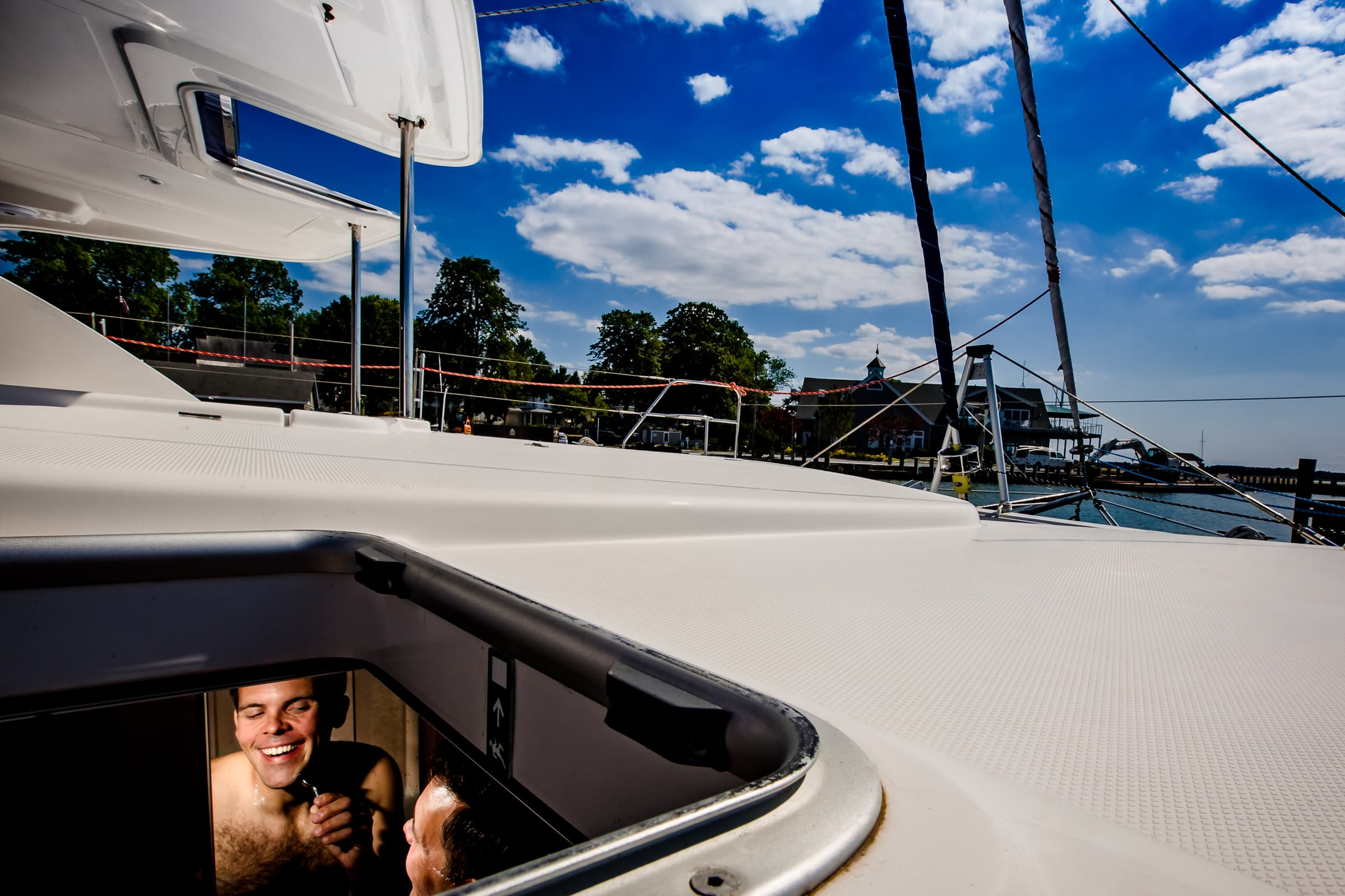 Groom shaving on a catamaran sailboat photographed thru a port hole for their Chesapeake Bay Wedding