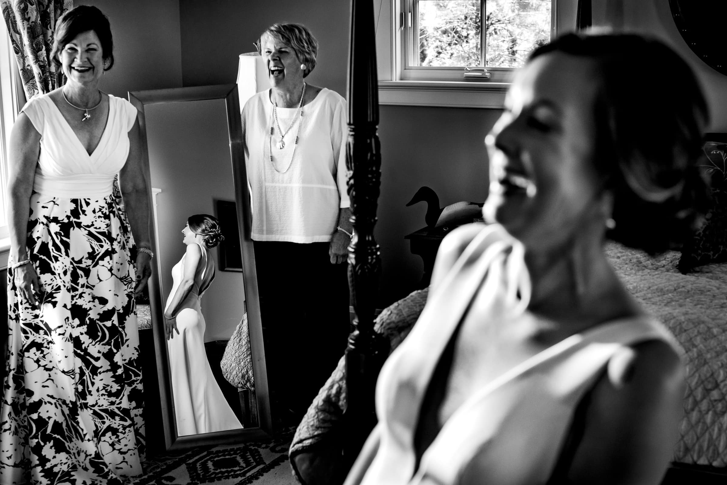 Bride laughing with moms while getting ready for her Chesapeake Bay wedding in Maryland.