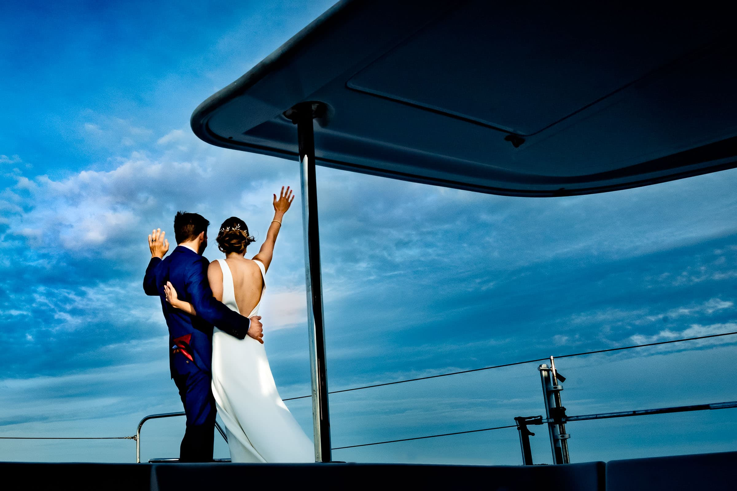 Bride and groom waving goodbye from their catamaran in Chesapeake Bay Maryland