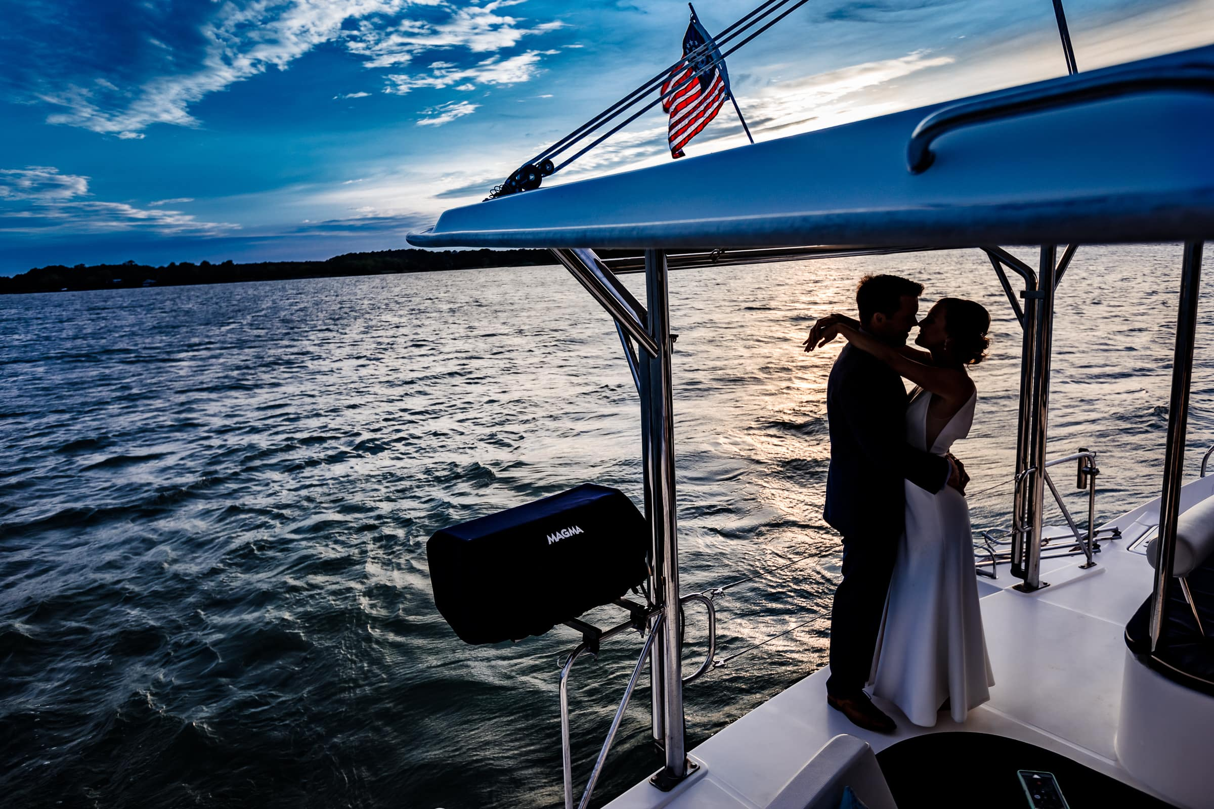 Silhouette of bride and groom on the back end of their catamaran sailboat for their Chesapeake Bay wedding.