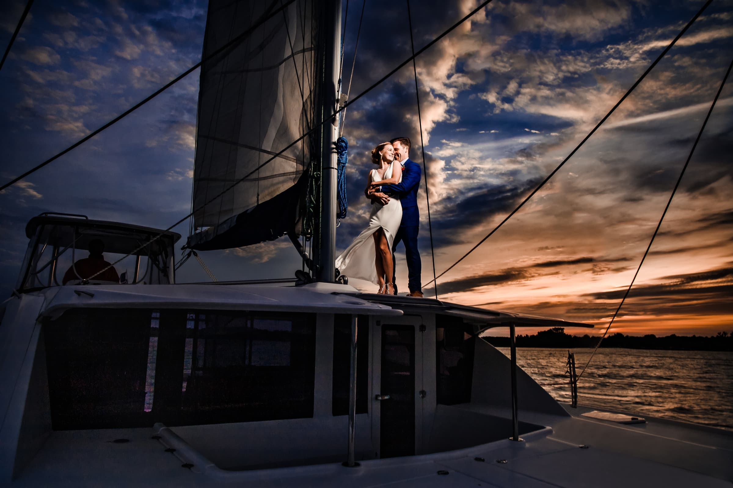 Beautiful portrait of bride and groom lit up at sunset on their catamaran sailboat for their Chesapeake Bay wedding.