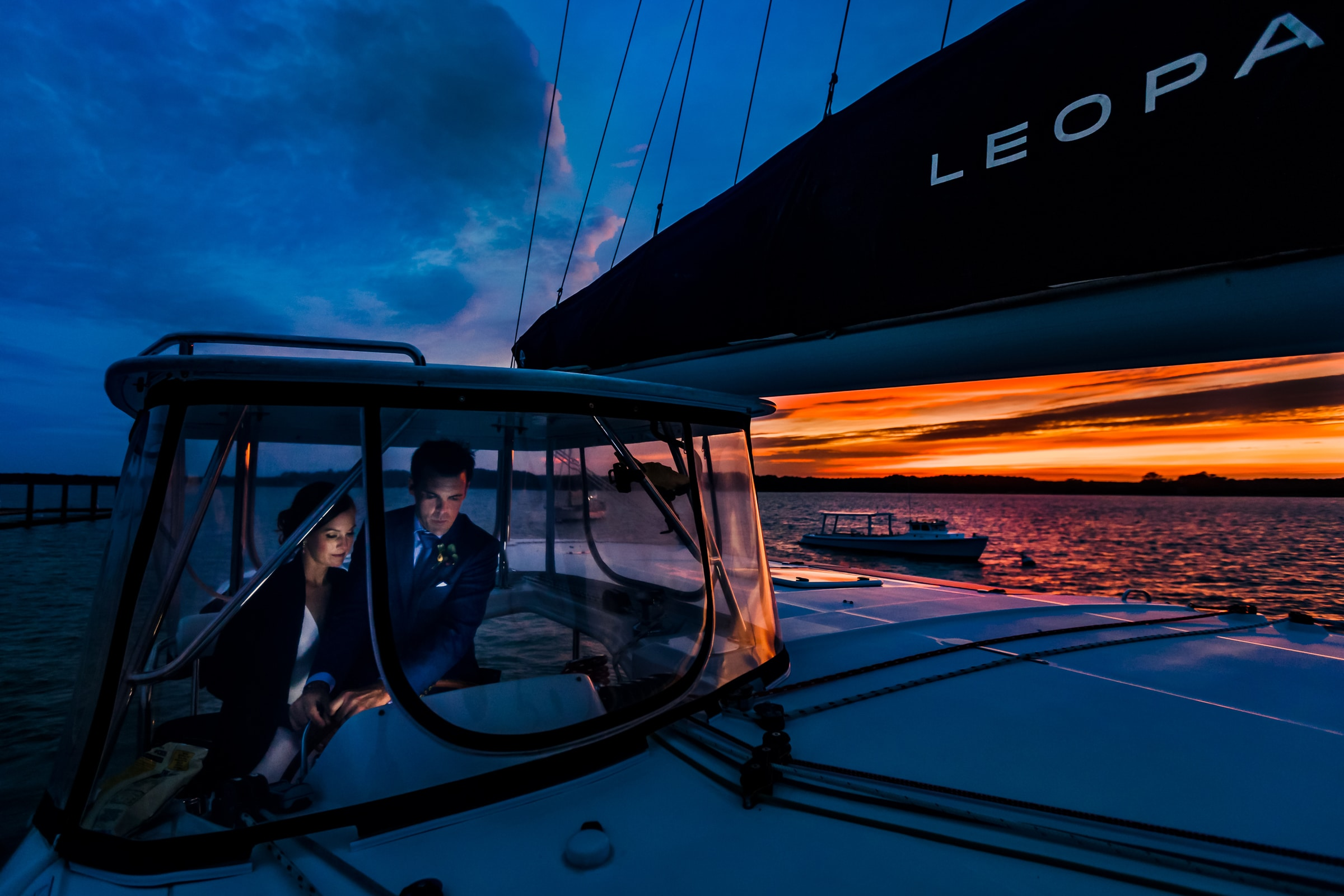Bride and Groom steering their catamaran boat at sunset for their Chesapeake Bay wedding.