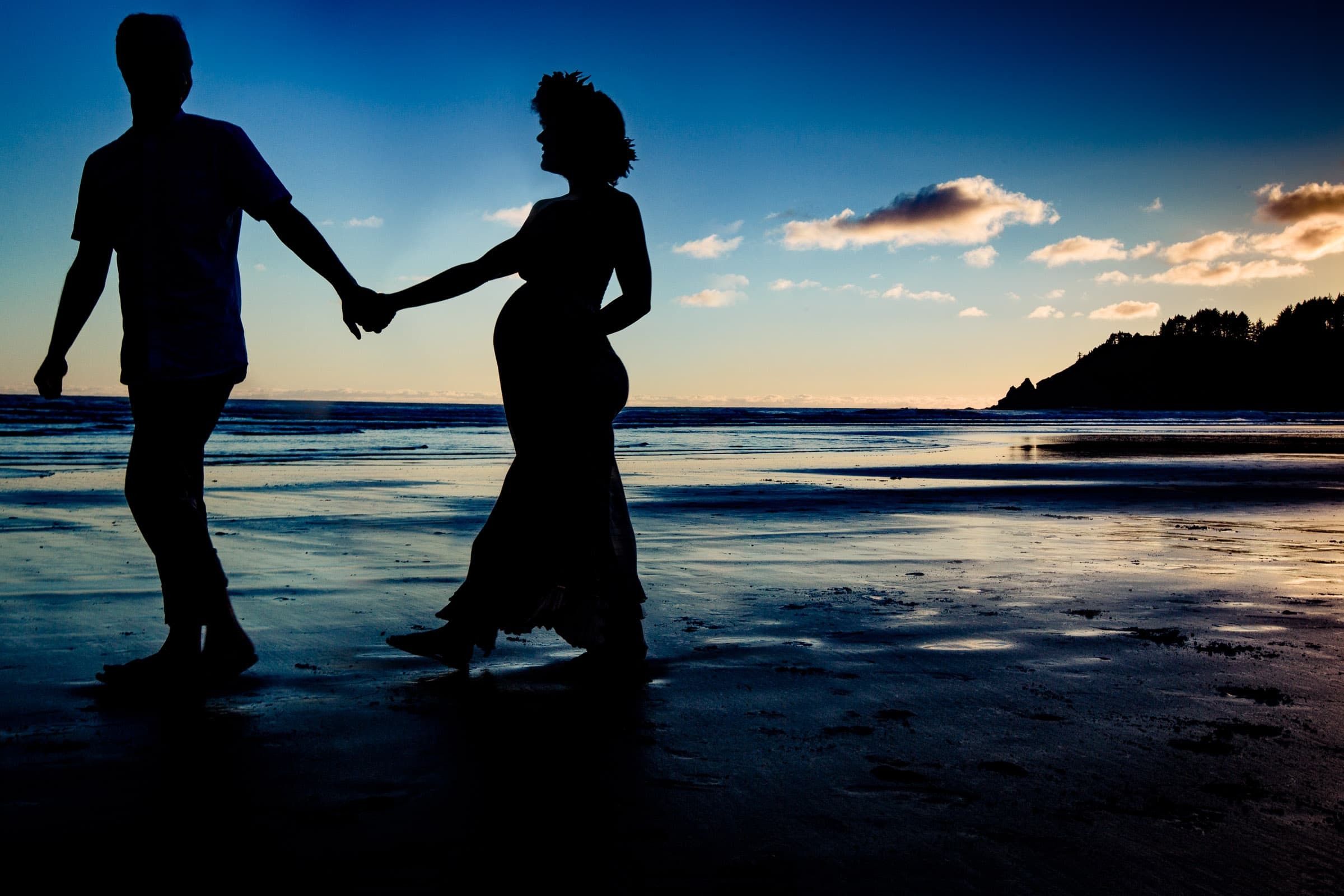A pregnant couple walking in a beautiful silhouette on Cannon beach Oregon for their maternity photos