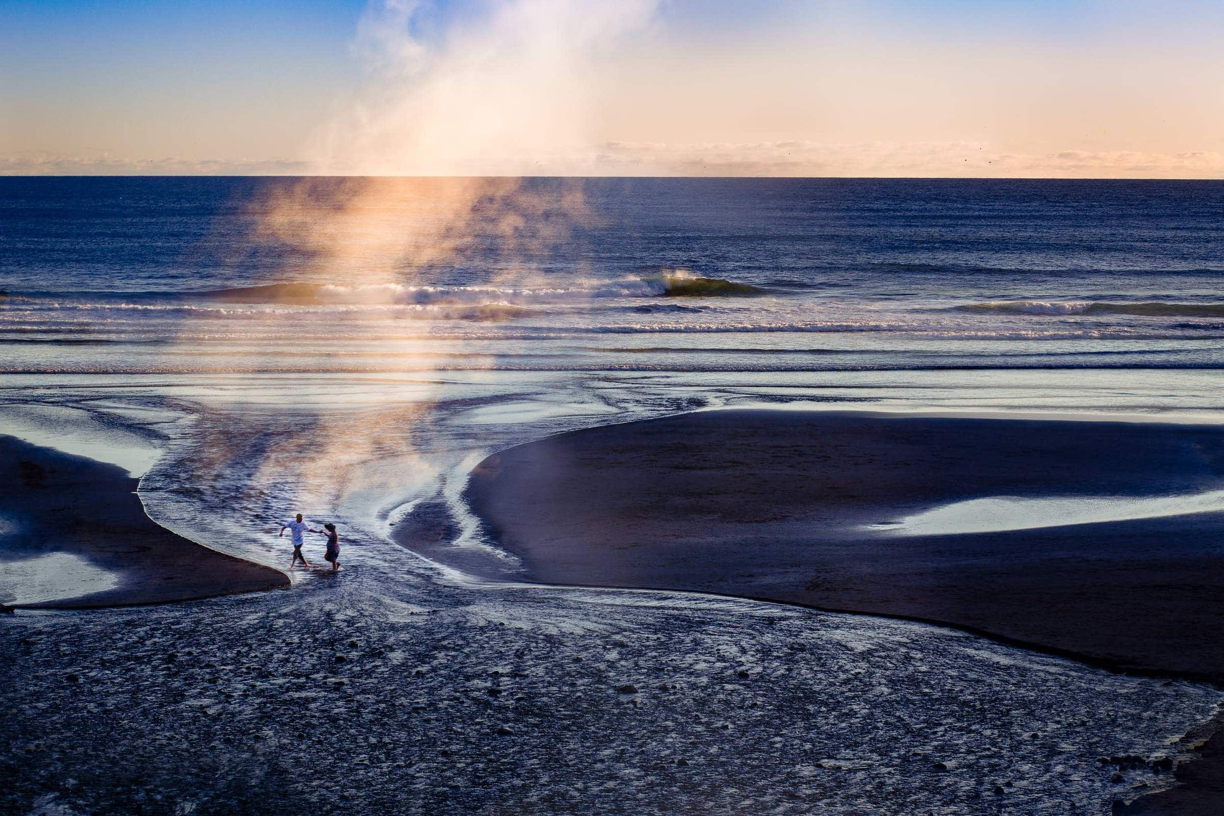 Epic photo of couple walking on beach for their maternity photos