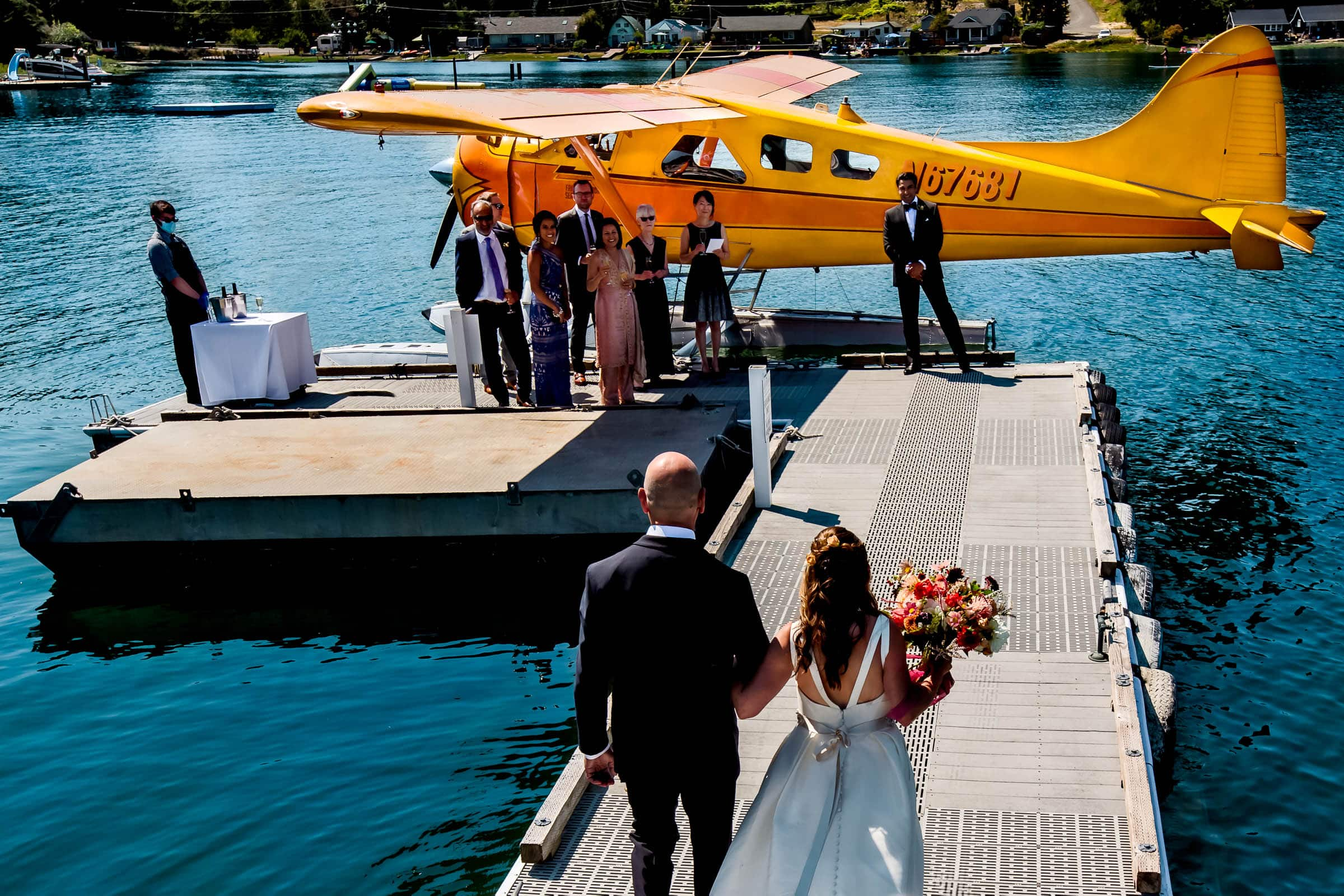 Bride and groom walking down a dock for an Alderbrook Elopement to a seaplane headed to Hope Island.