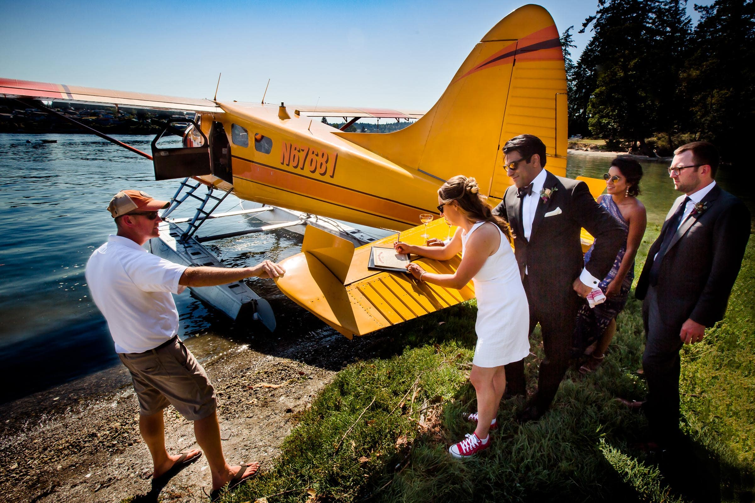 Bride and groom signing their wedding certificate on a seaplane wing on Hope Island for their Alderbrook Elopement.