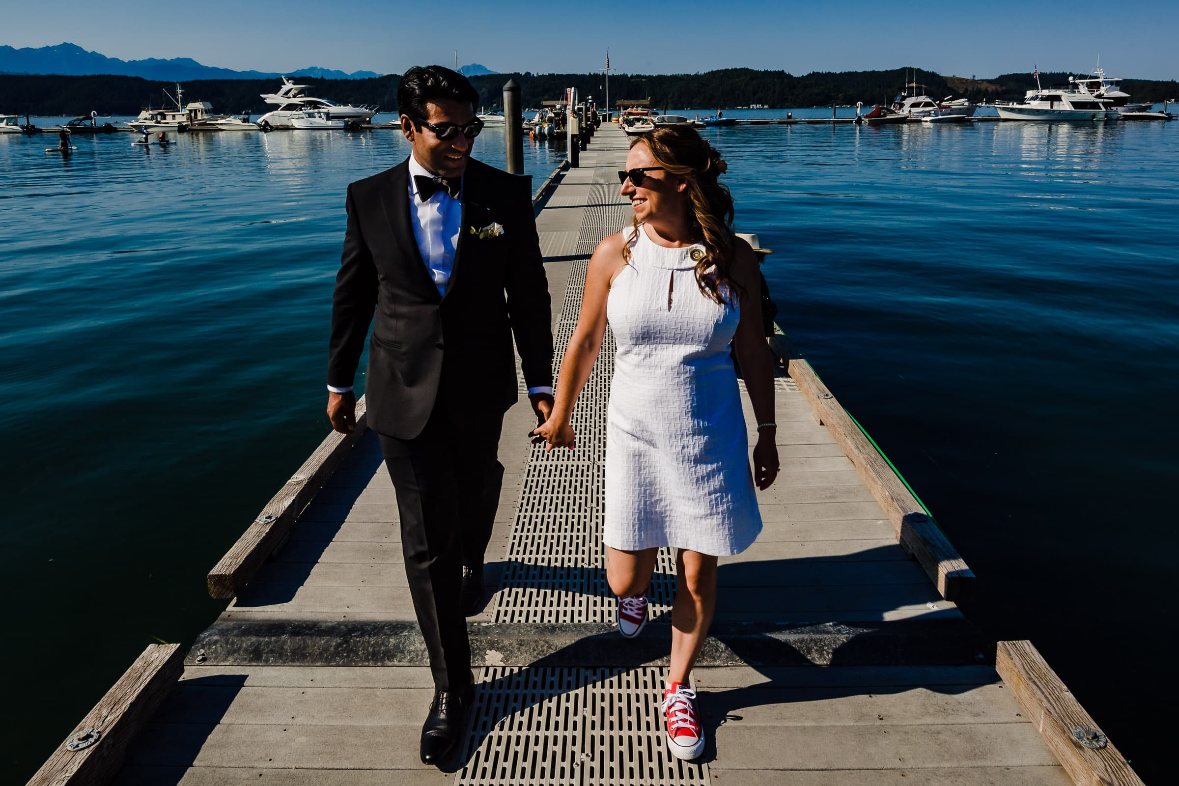 Bride and Groom walking on a dock headed to the Gathering Grove for their dinner during their Alderbrook elopement.