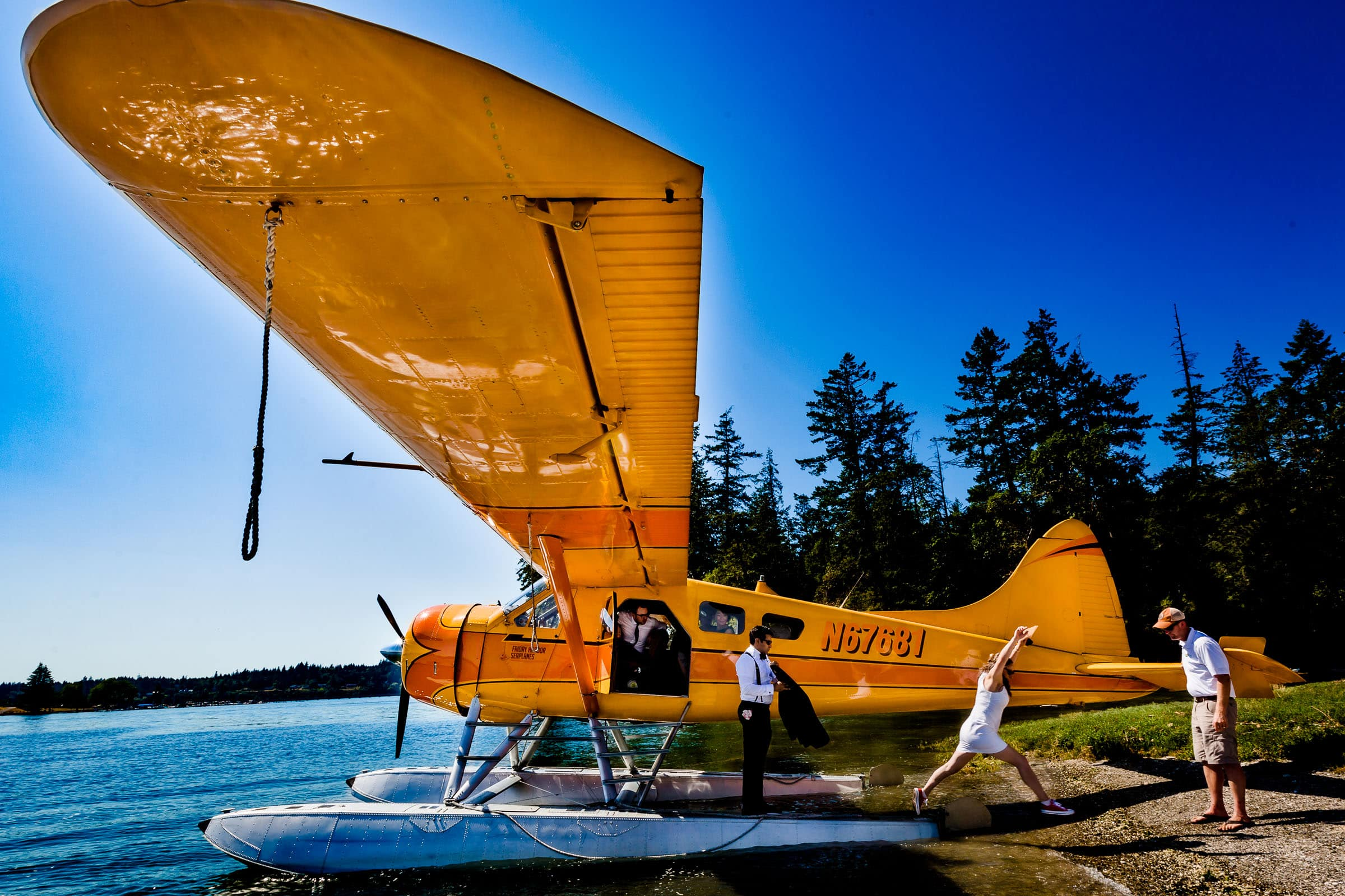 bride jumping off seaplane onto Hope Island during Alderbrook elopement