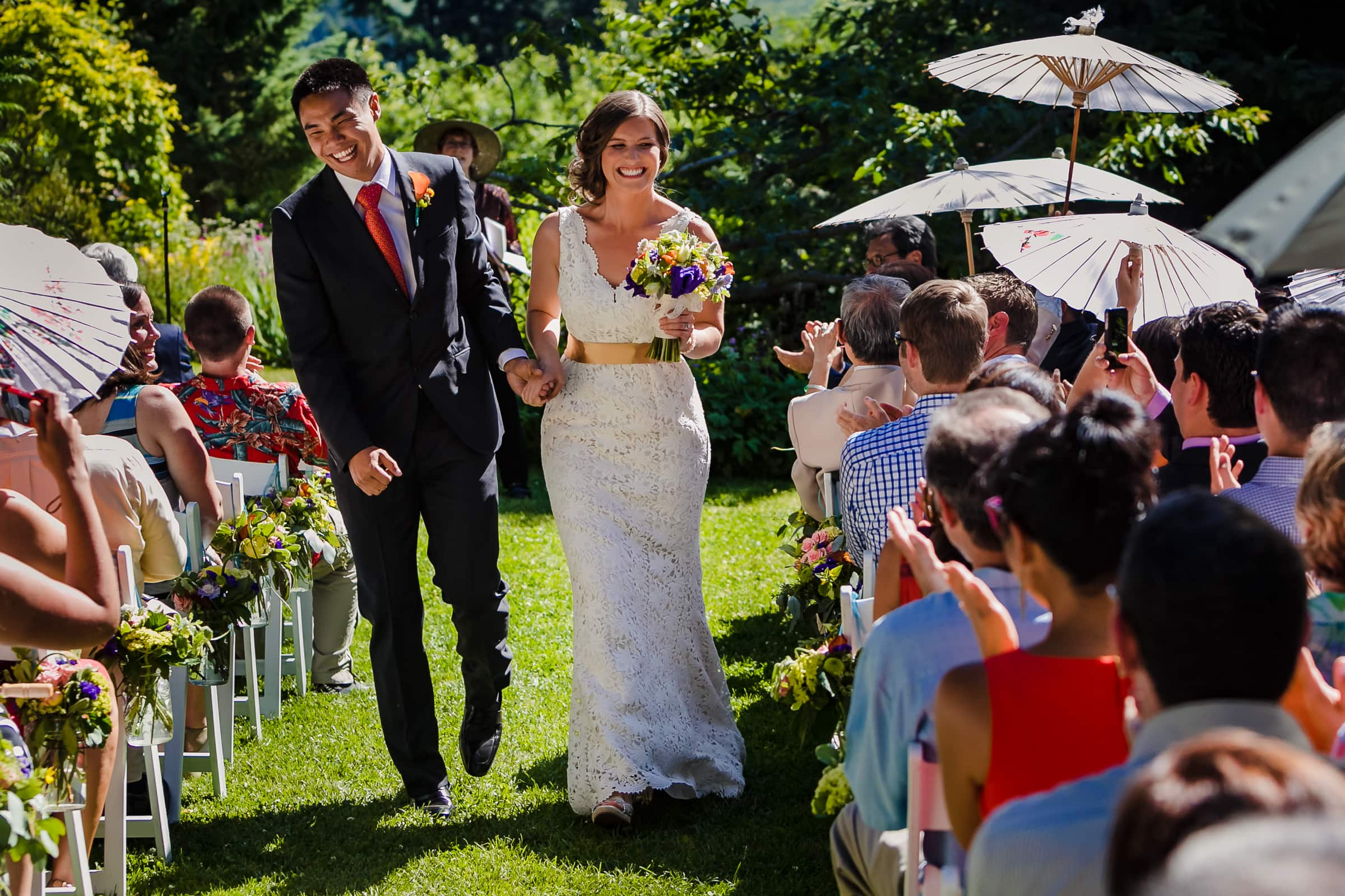 Bride and groom laughing together while exiting their Mt Hood Organic Farms Wedding ceremony