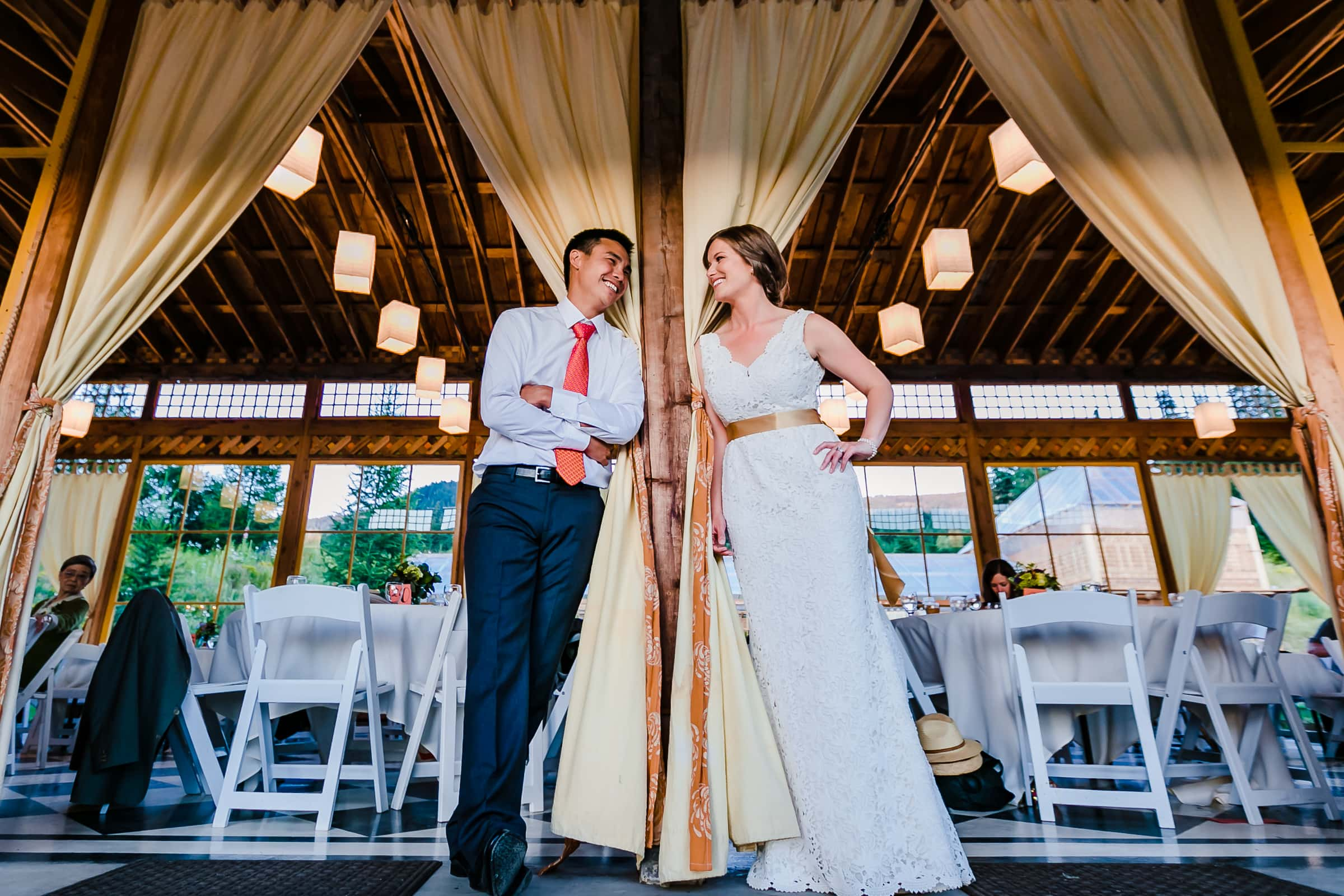 Bride and groom near drapes during their Mt Hood Organic Farms reception dinner