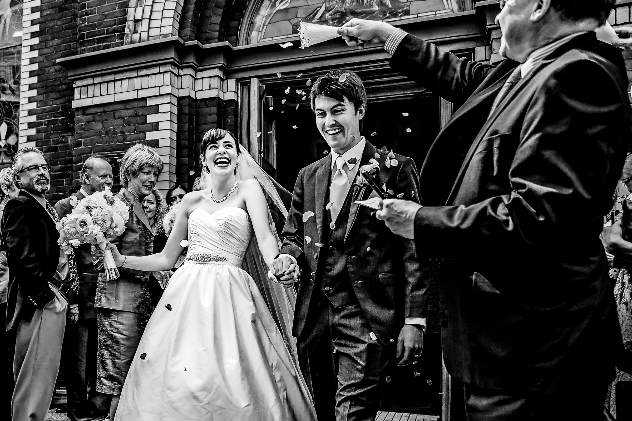 A fun and exciting photo of bride and groom exiting out of the First Presbyterian Church in Portland while heading to their Waverley Country Club wedding