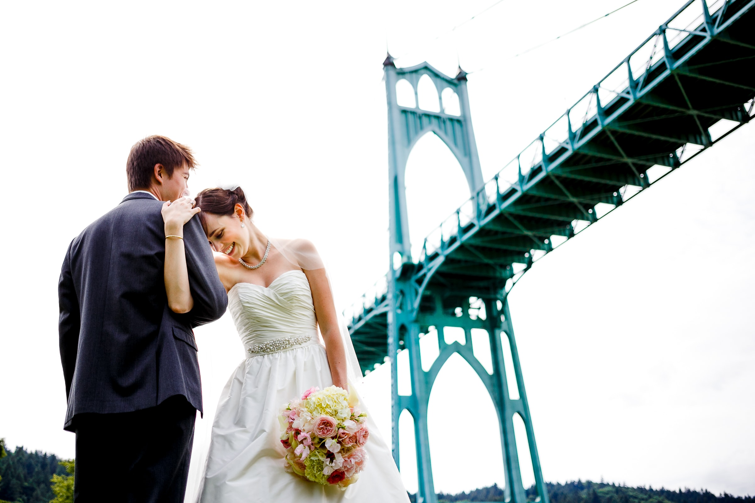 Bride and groom having a moment together under the St John's Bridge in Portland before heading to their Waverley Country Club wedding