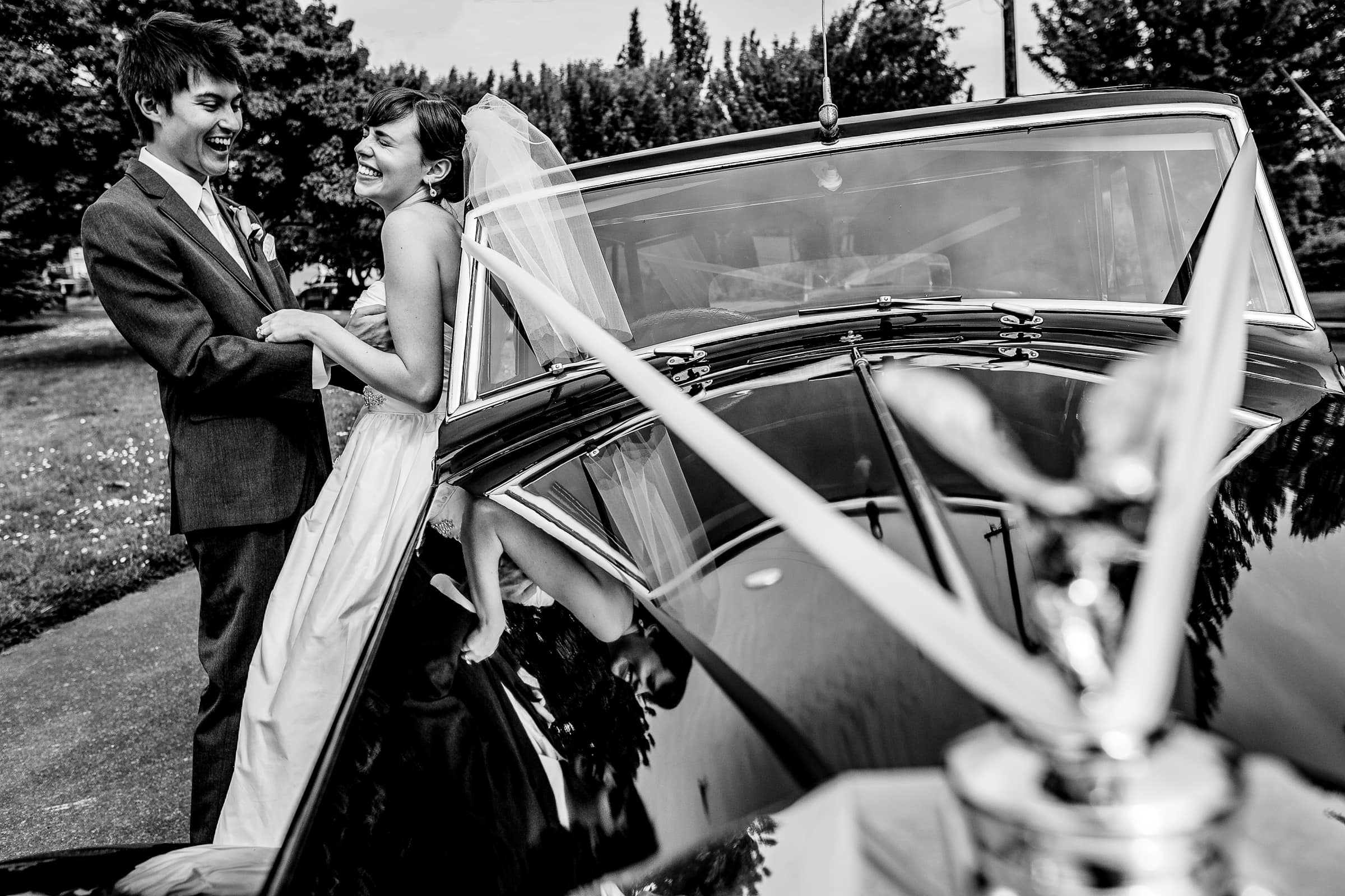 Bride and groom having a moment together with a limousine car the St John's Bridge in Portland before heading to their Waverley Country Club wedding