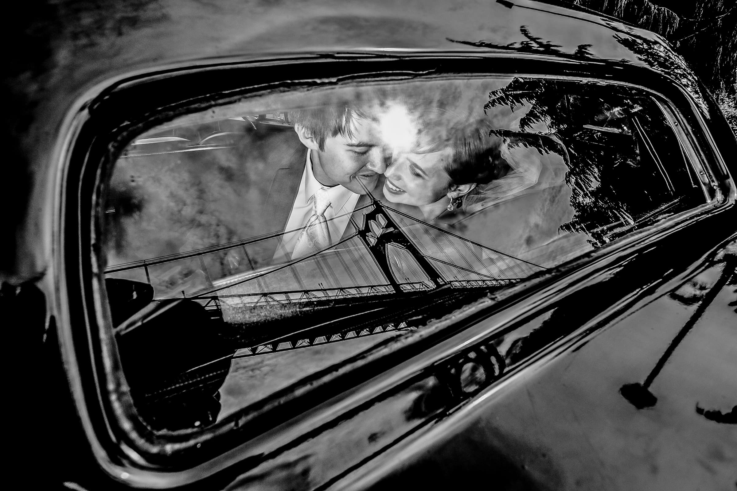 Bride and groom faces reflecting in a limousine back window together under the St John's Bridge in Portland before heading to their Waverley Country Club wedding