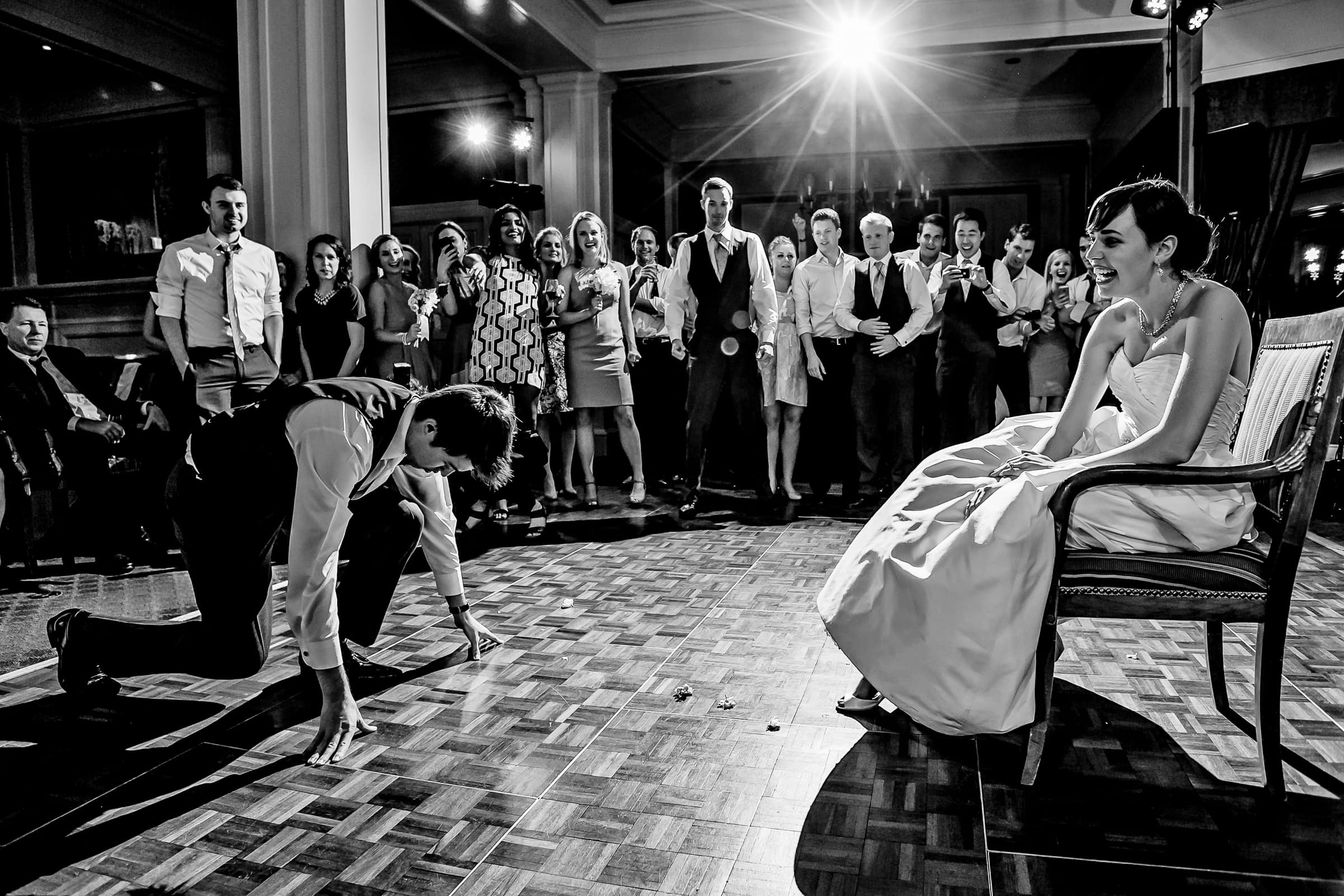 A comical photo of a groom getting ready in a football stance ready to take the garter off his bride at their Waverley Country Club wedding reception in Lake Oswego, Oregon