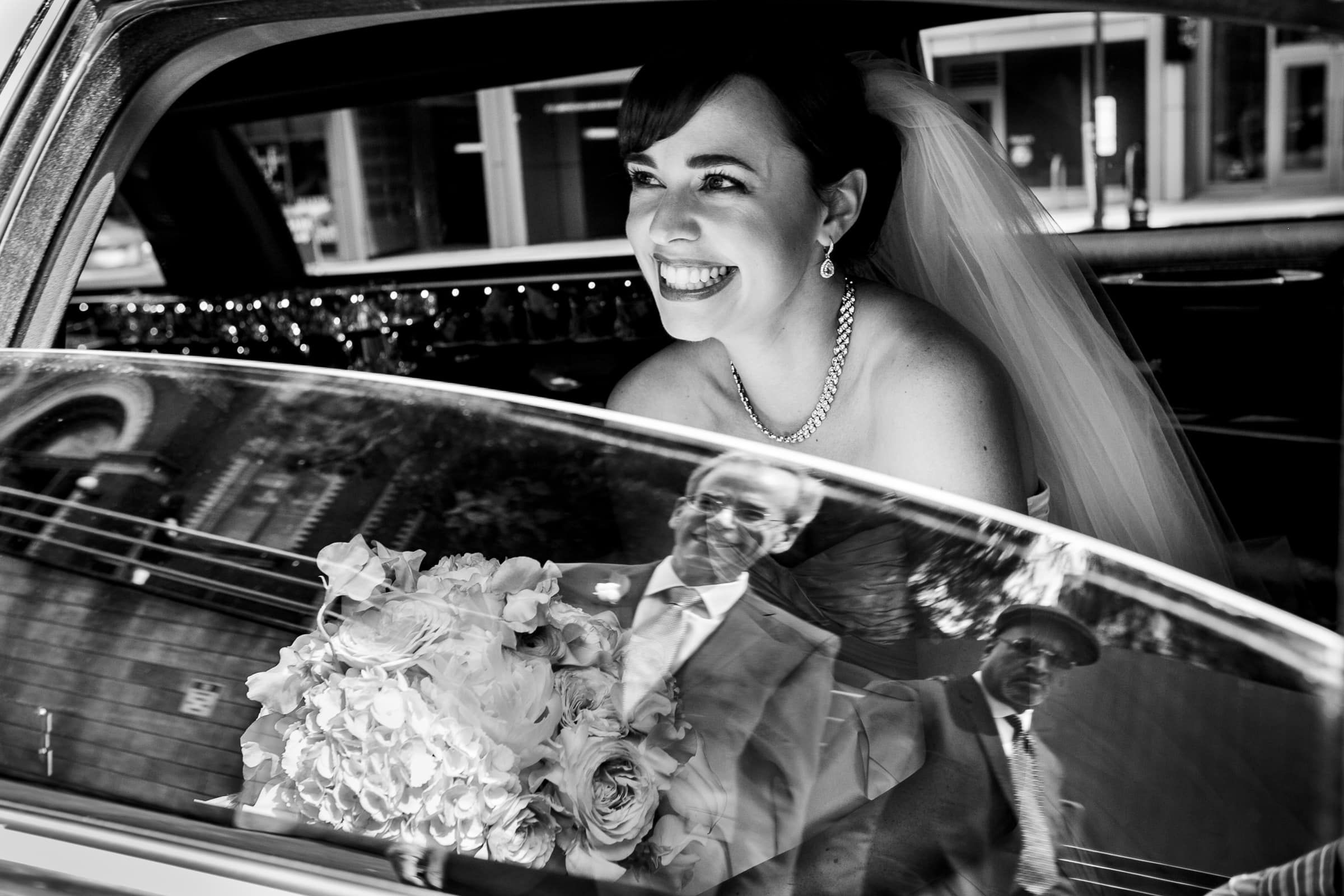 Reflection of a father in a limousine window  seeing his emotional daughter as a bride heading into her Waverley Country Club wedding