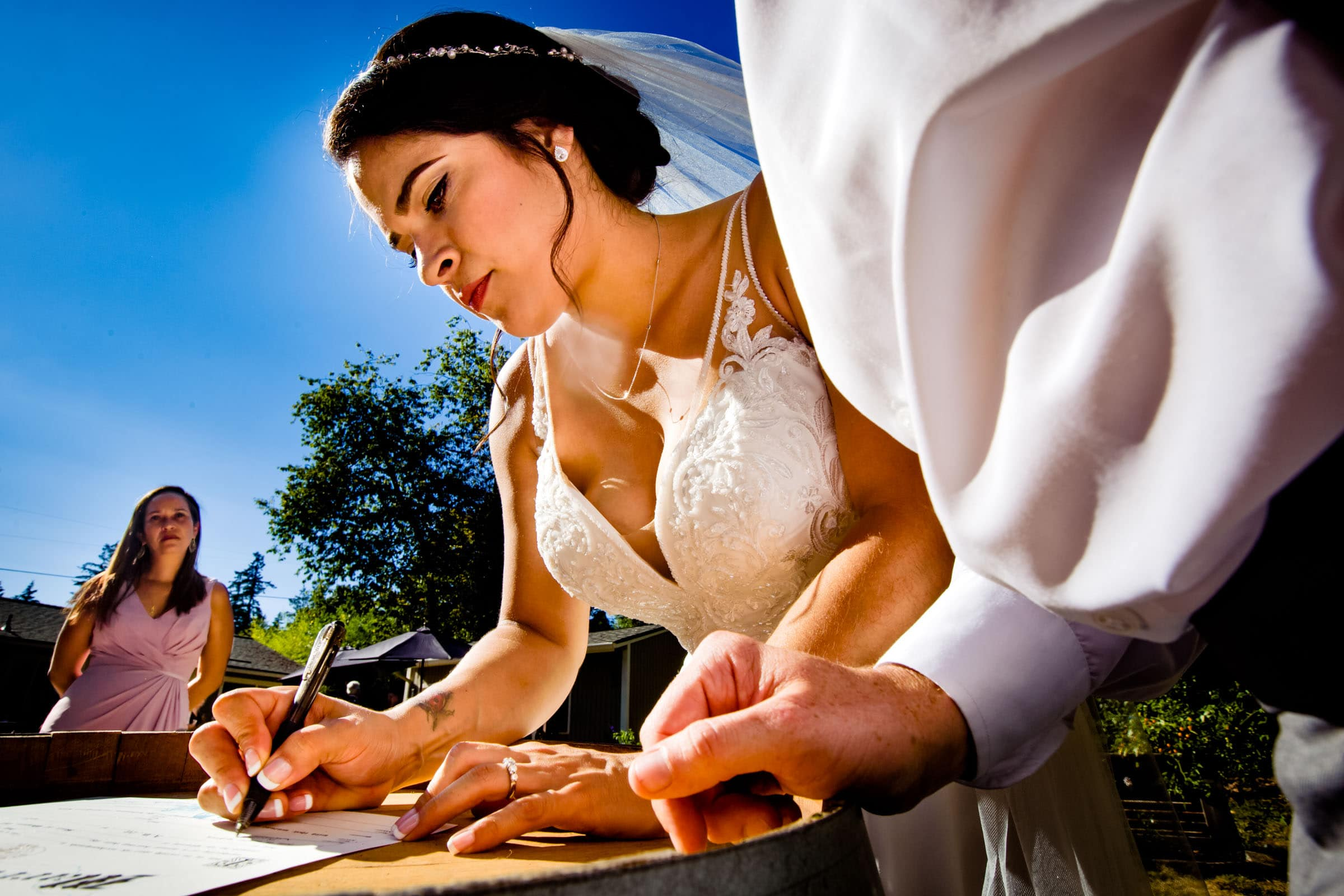 Bride signing marriage certificate during her Portland Elopement during COVID