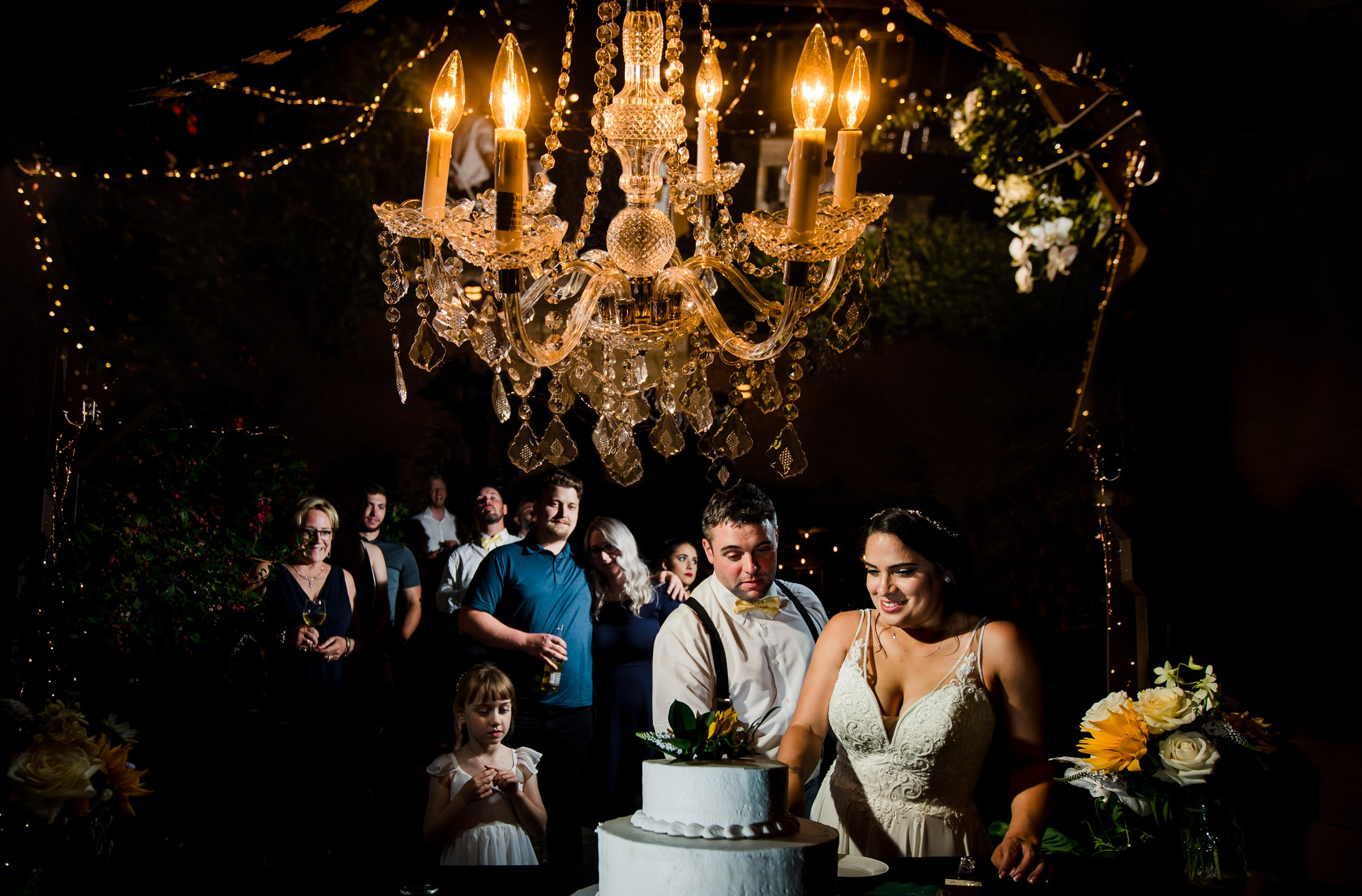 Bride and groom cutting a cake under a chandelier during their Portland Wedding elopement