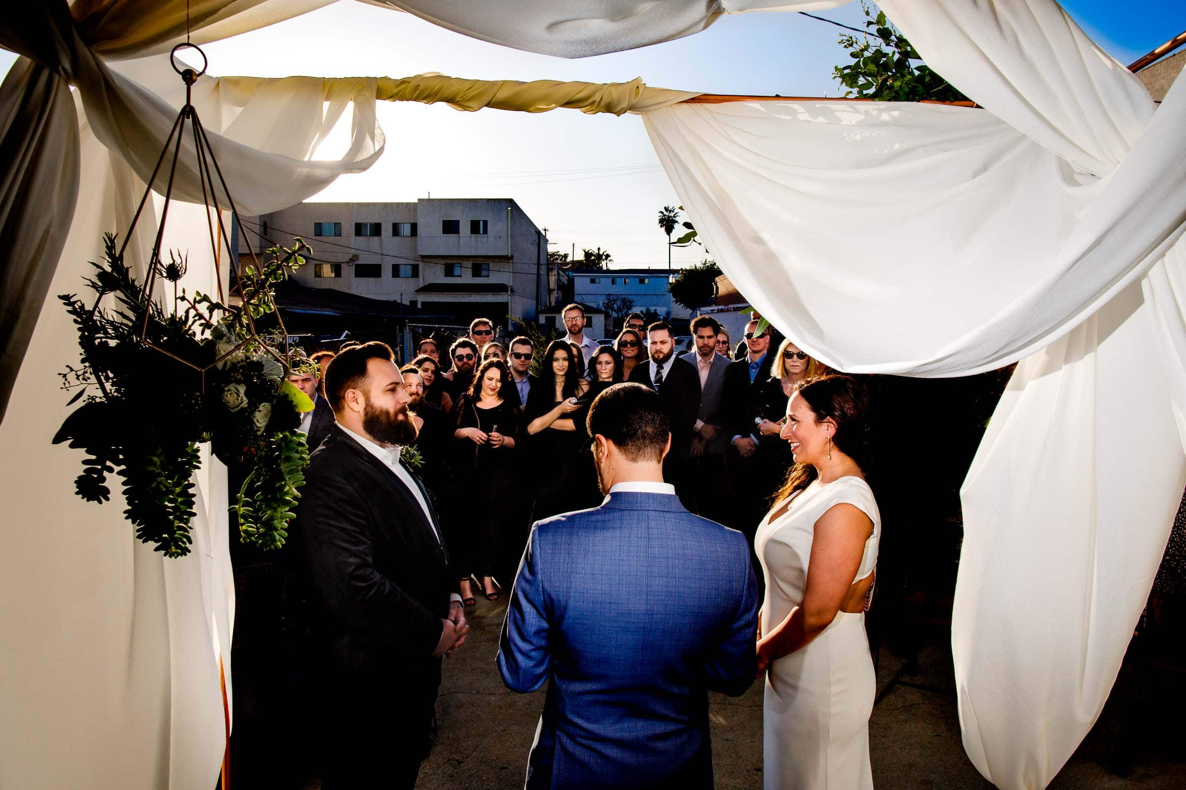 Bride and groom exchanging vows during their Los Angeles Wedding ceremony with family and friends all surrounding them.