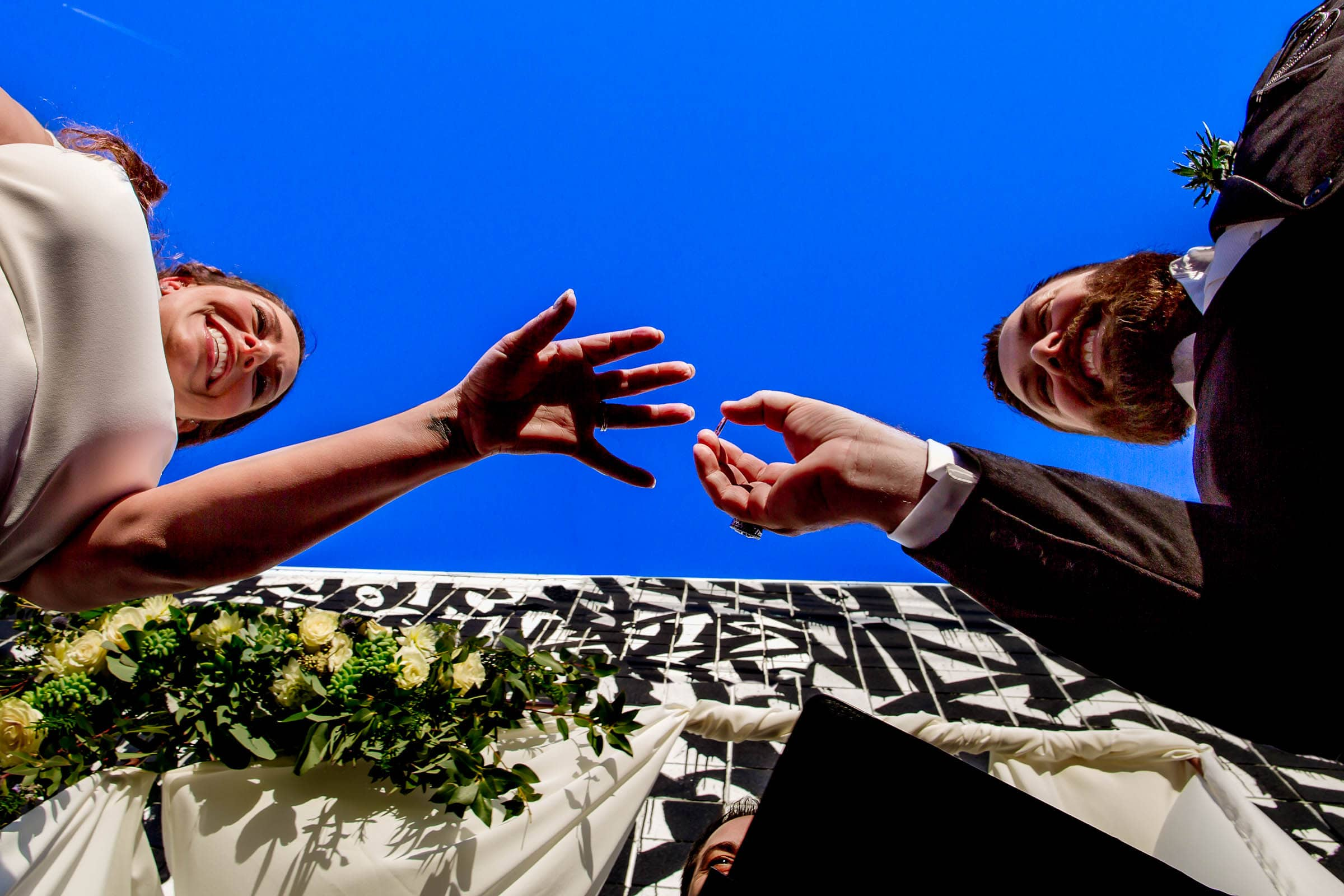 Bride and groom exchanging rings during their Los Angeles Wedding ceremony with family and friends all surrounding them.