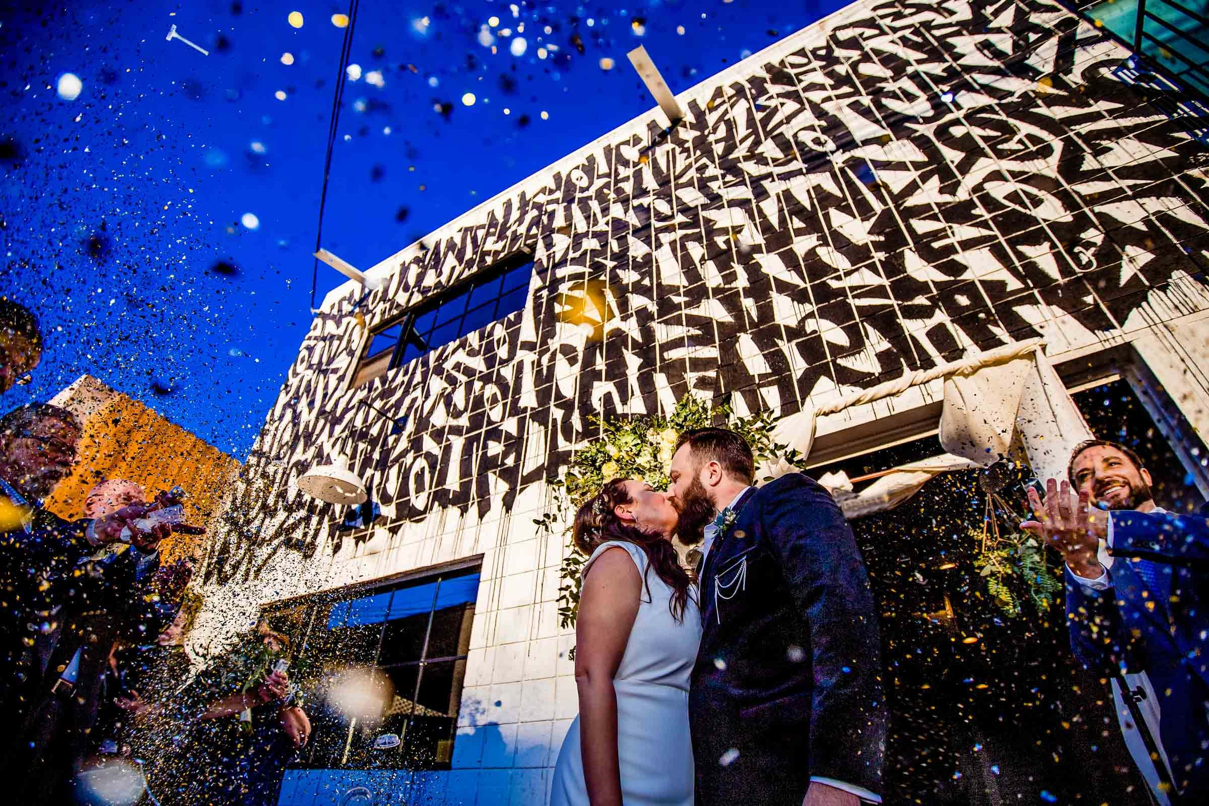 Bride and groom kissing with confetti flying during their Los Angeles Wedding ceremony with family and friends all surrounding them.