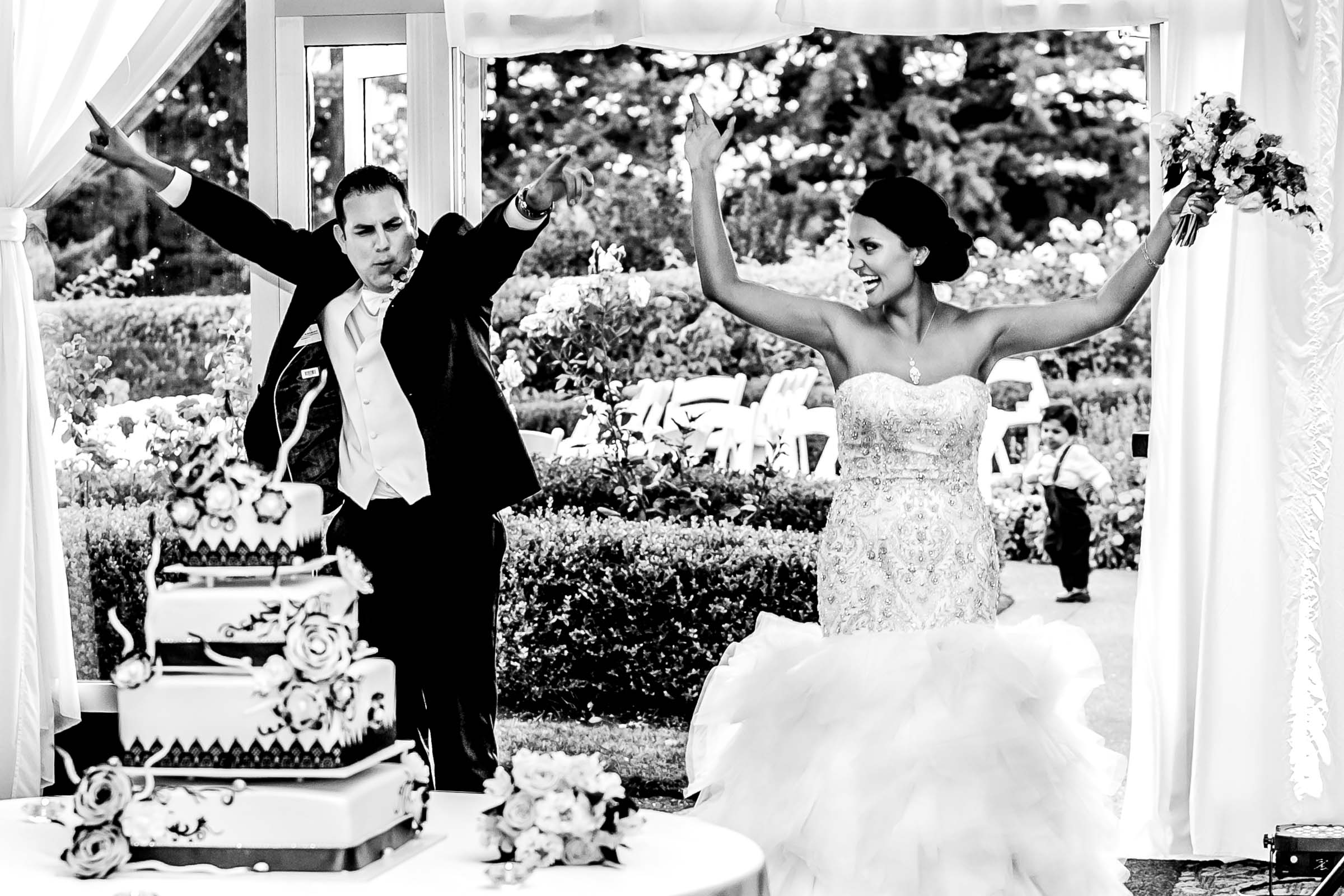 Bride and groom entering their Oregon Golf Club wedding reception with their hands up near a big cake