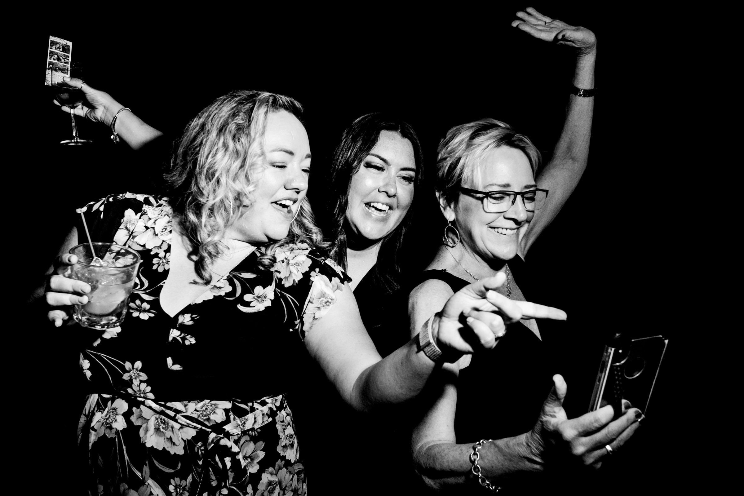 women laughing with cell phones during wedding reception in Portland Oregon