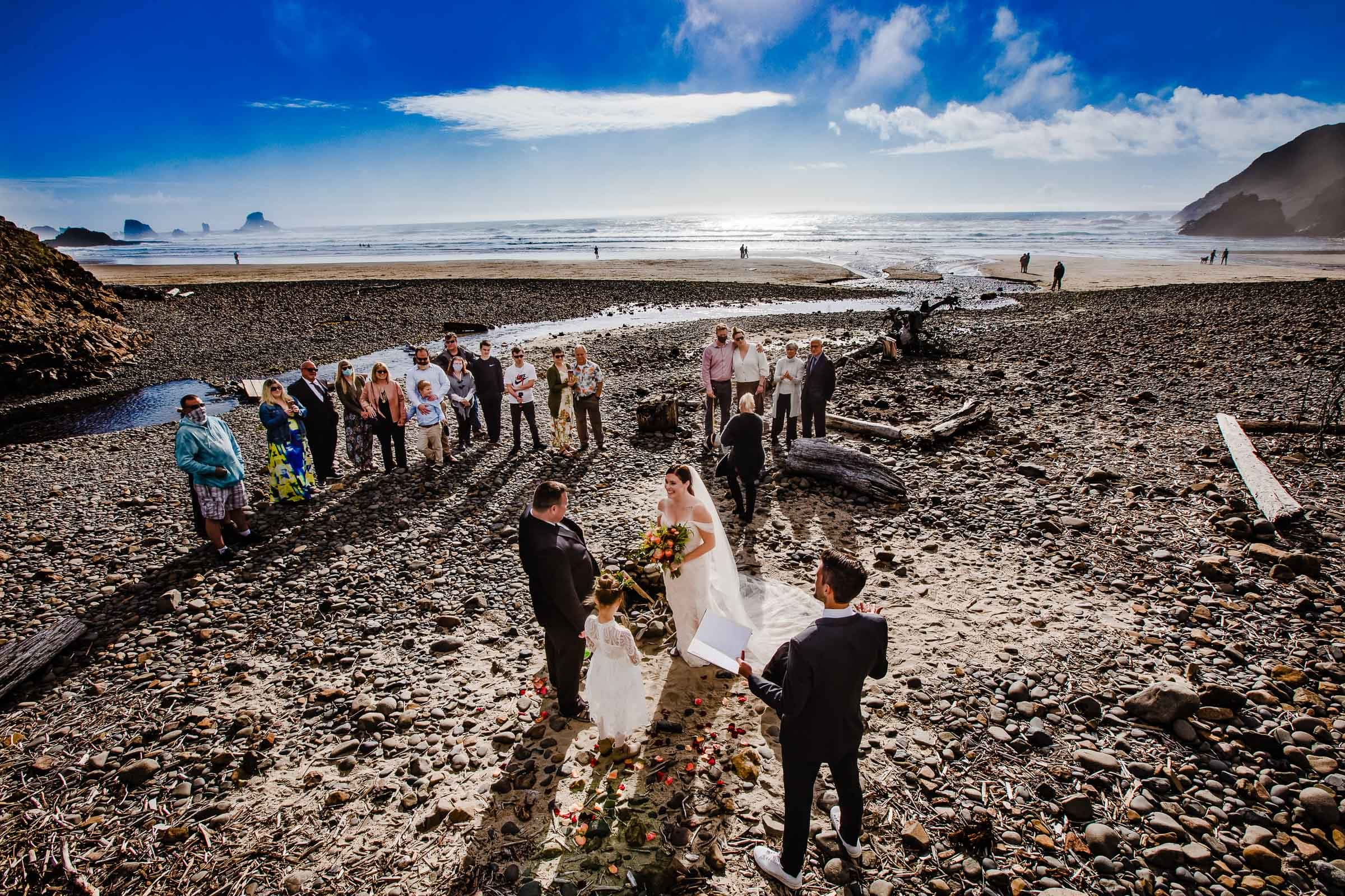 Oregon Coast Elopement ceremony at Cannon Beach with bride and groom and guests with ocean in background