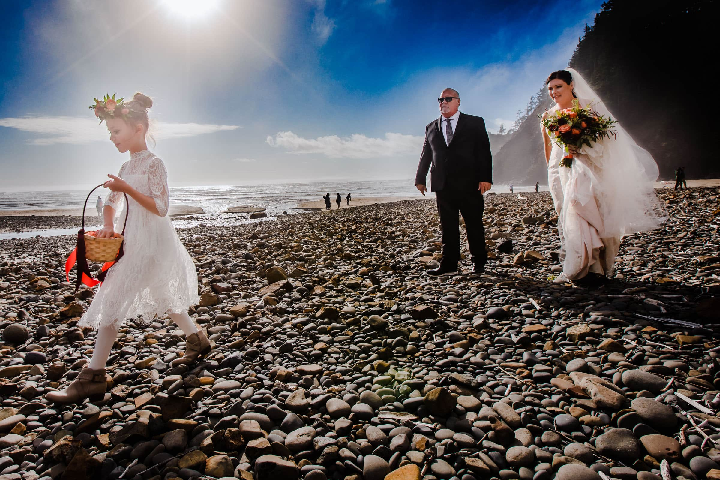 bride and father and daughter walking on beach into Cannon Beach elopement ceremony