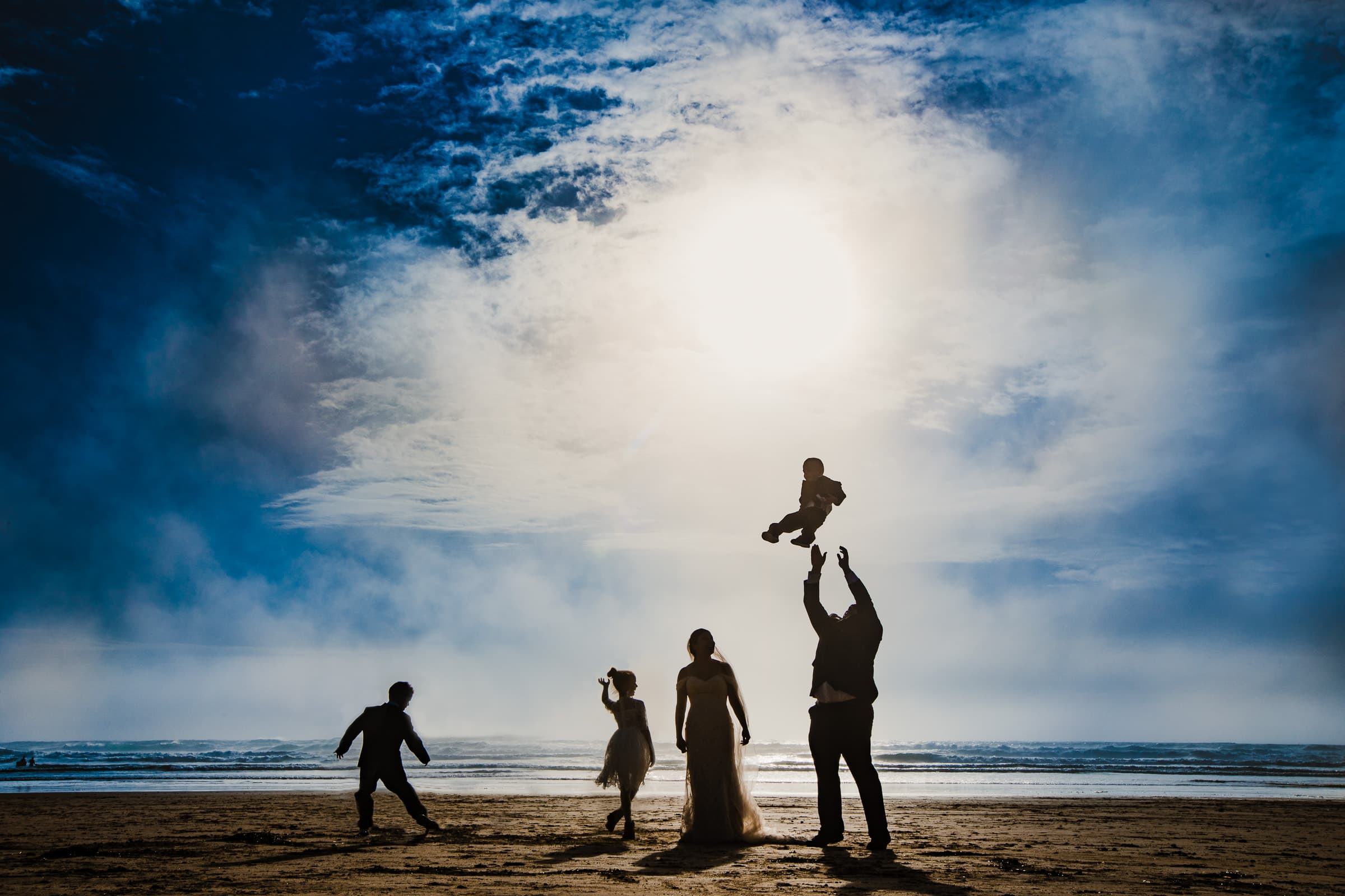 groom throwing son into the sky during cannon beach elopement