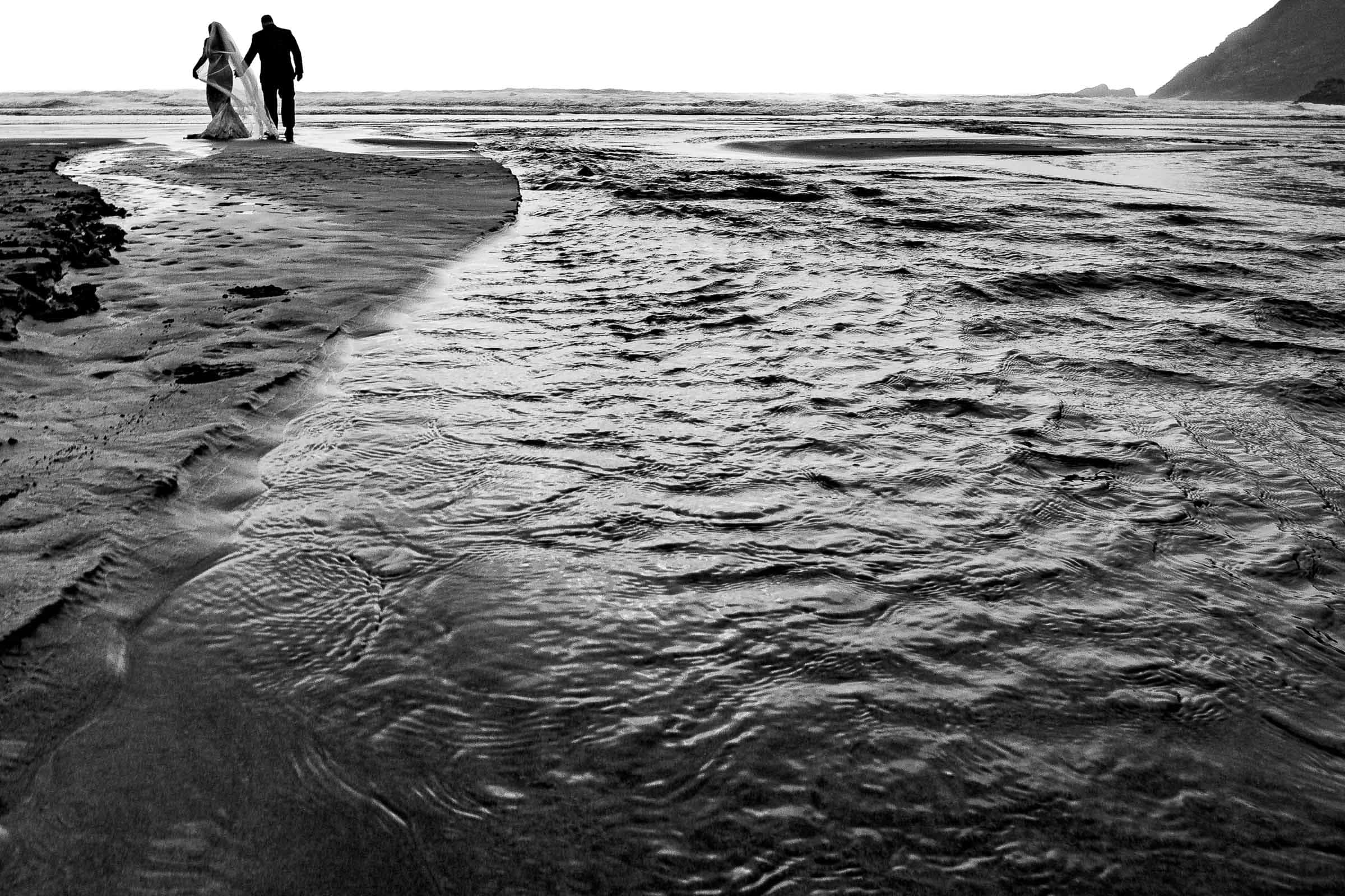 bride and groom walking into a dramatic sunset on Cannon Beach during their elopement