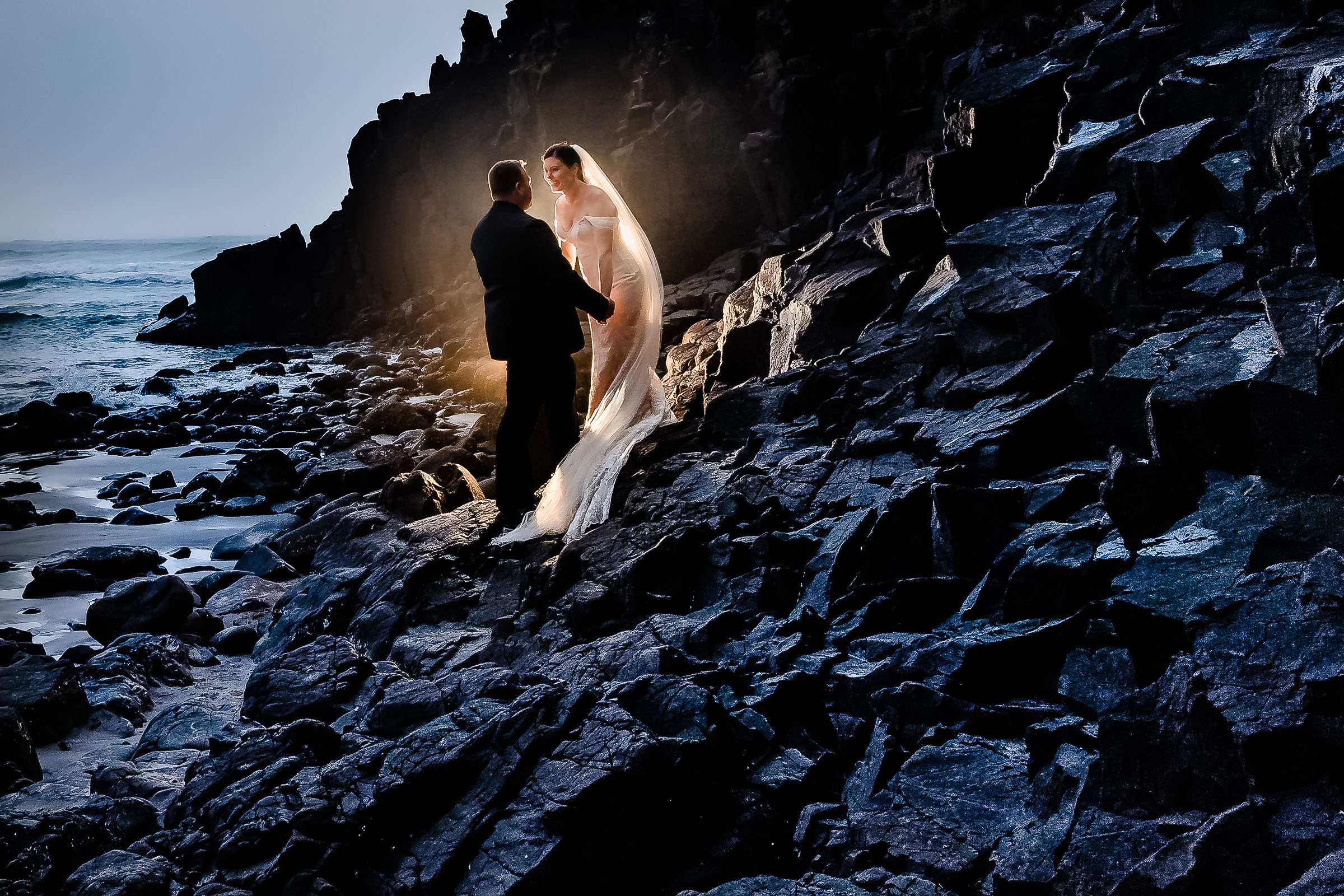Bride and groom on rocks with beautiful warm backlight wrapping around them at Ecola State Park for their Cannon Beach elopement