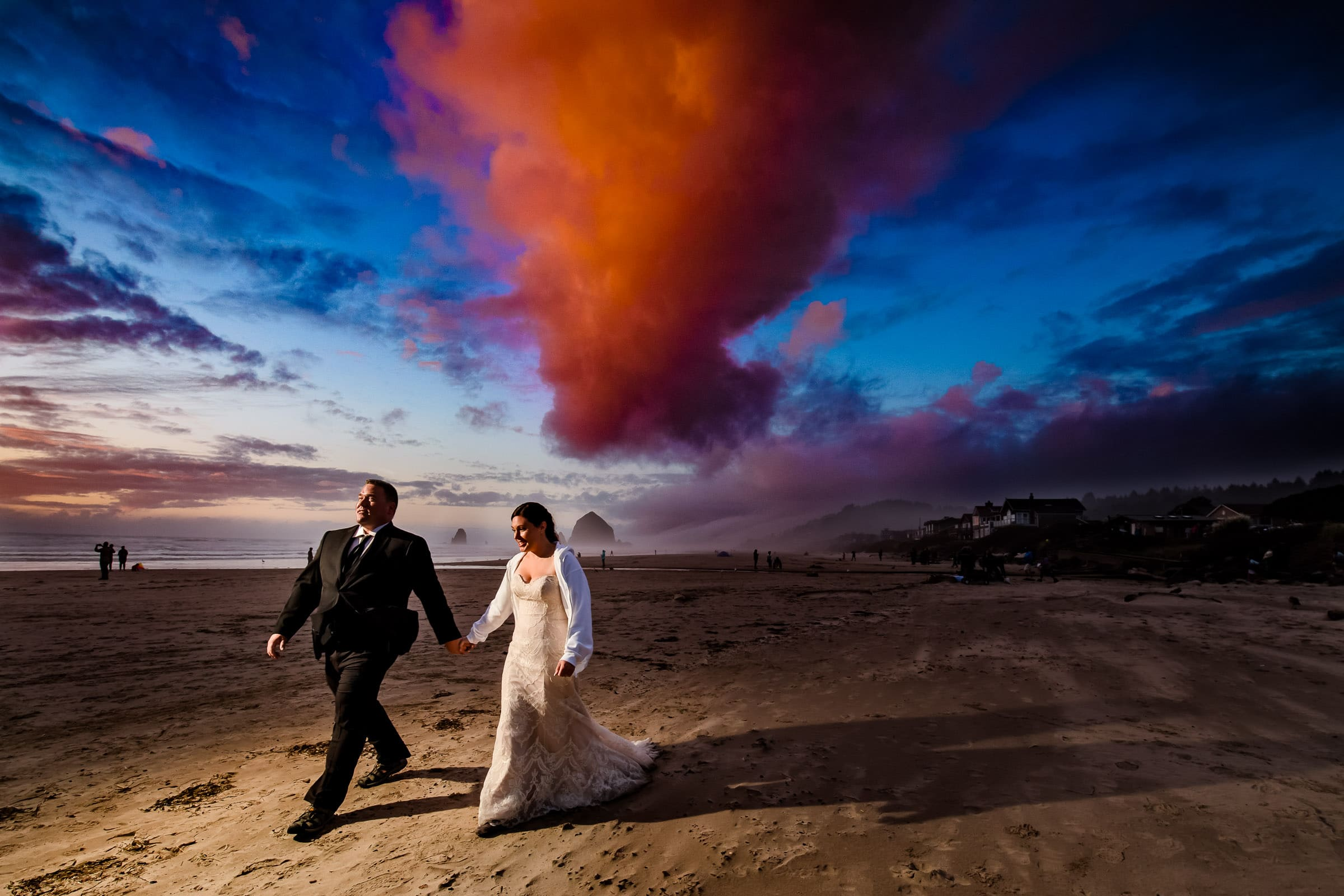 Cannon Beach Elopement of bride and groom walking on beach with colorful sunset in Oregon for their elopement