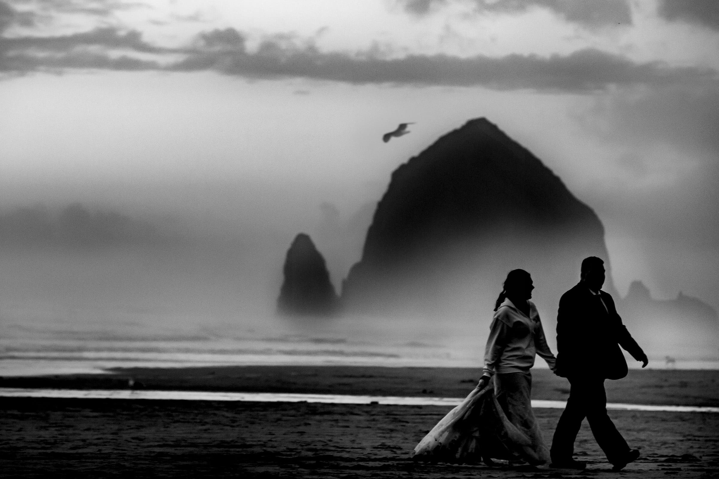 Dramatic portrait of bride and groom walking on beach during their cannon beach elopement