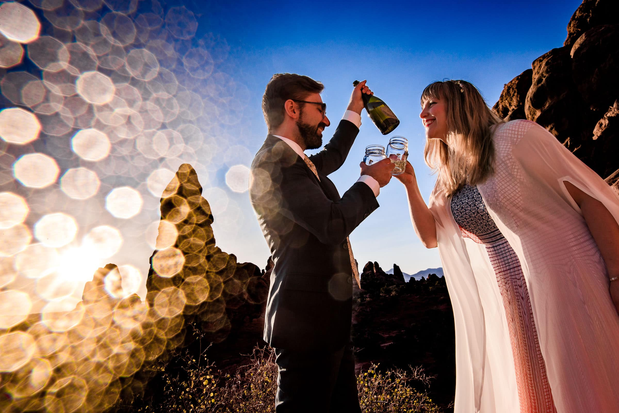 Bride and groom celebrating a champagne toast in Arches National Park during their adventure elopement in Moab, Utah.