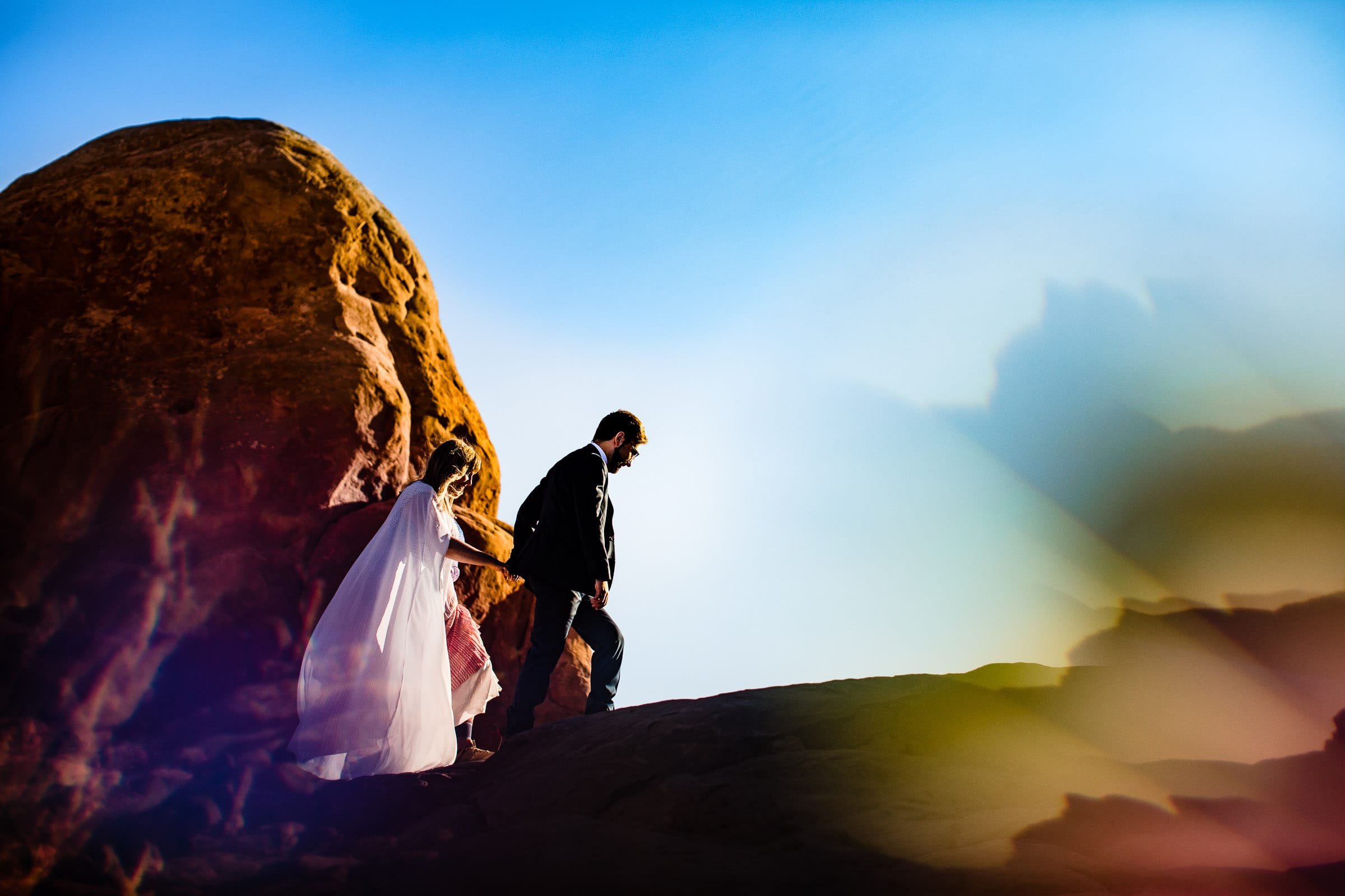 Bride and groom walking underneath the famous Windows section in Arches National Park in Moab for their adventure elopement