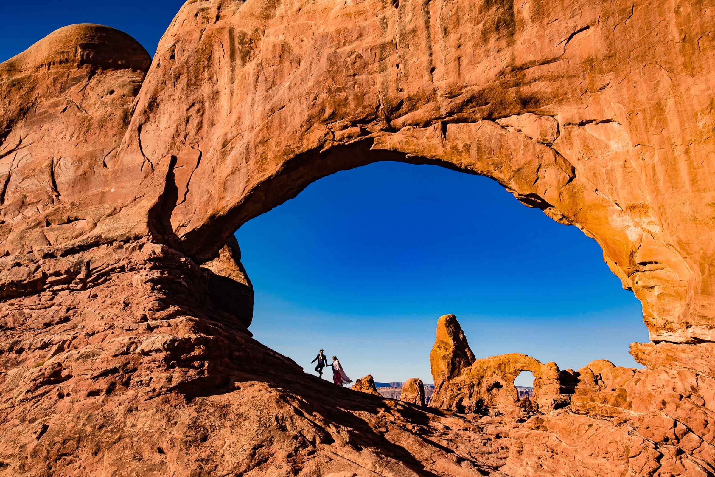 Bride and groom walking hand and hand under the famous Windows Section of Arches National Park in Moab Utah for their adventure elopement
