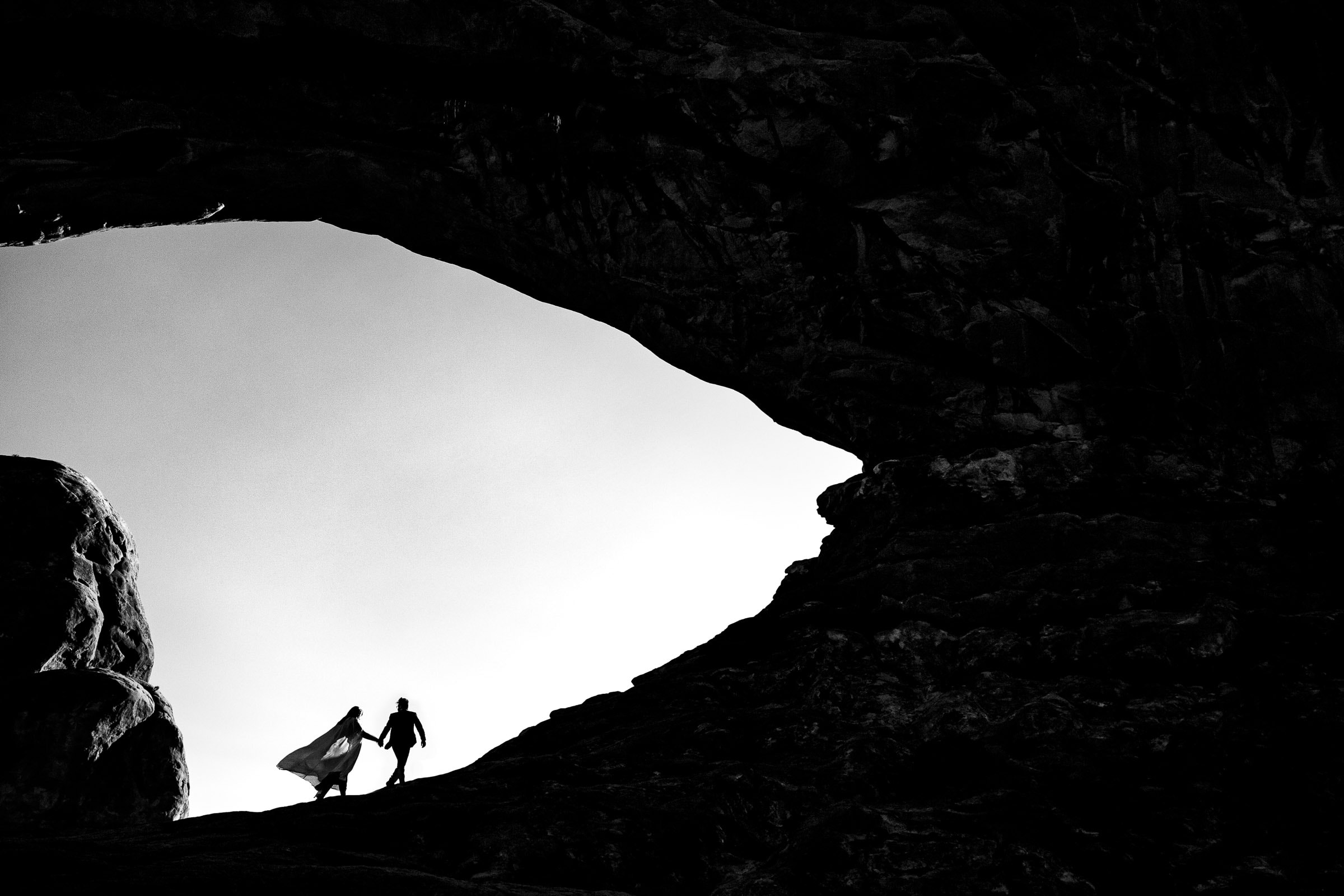 Bride and groom walking through Arches National Park in Moab Utah during their adventure elopement