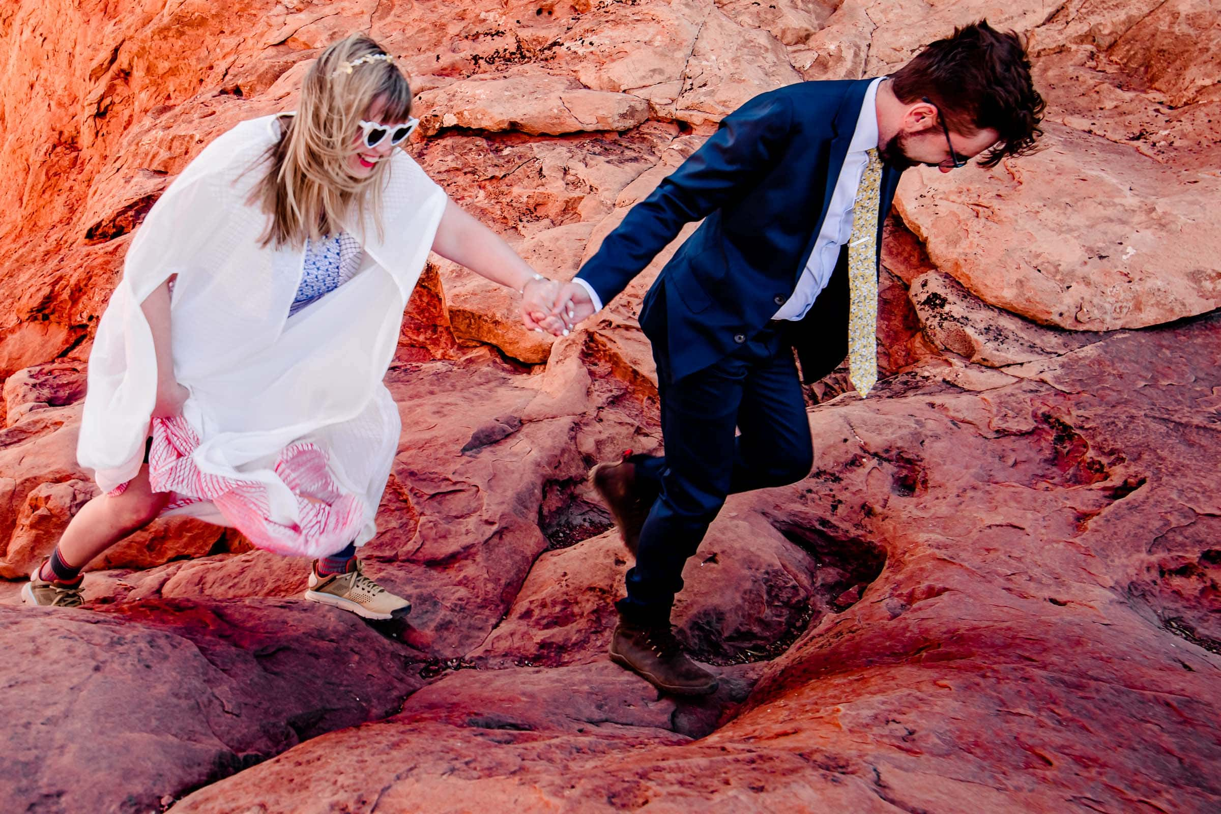 Bride and groom walking hand and hand through Arches National Park in Moab Utah during their adventure elopement