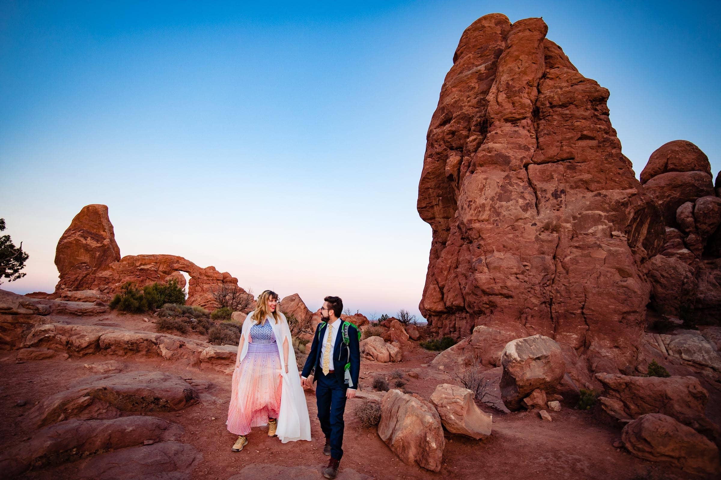 Bride and groom walking through Arches National Park for their adventure elopement.