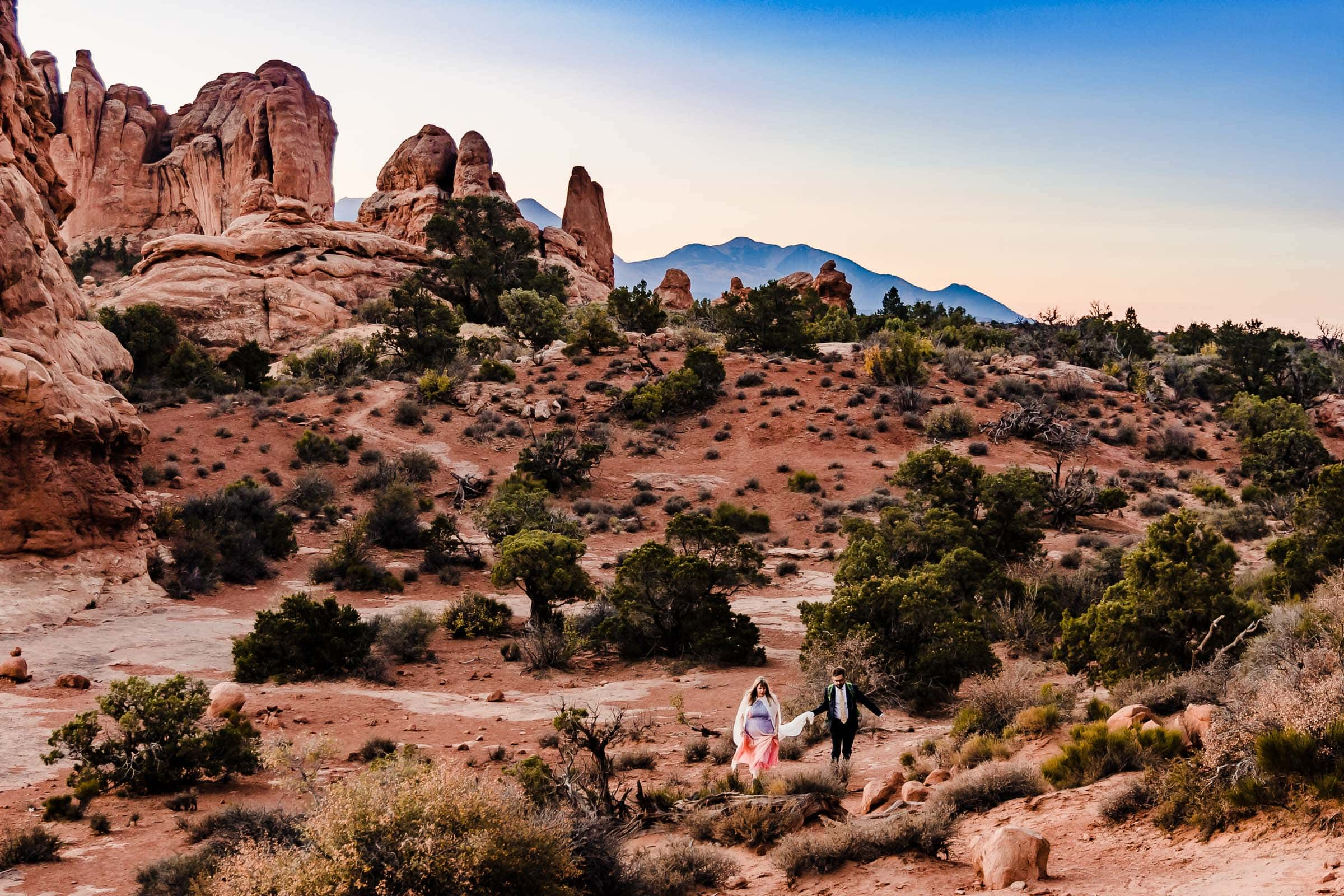 Bride and groom walking through Arches National Park for their wedding elopement