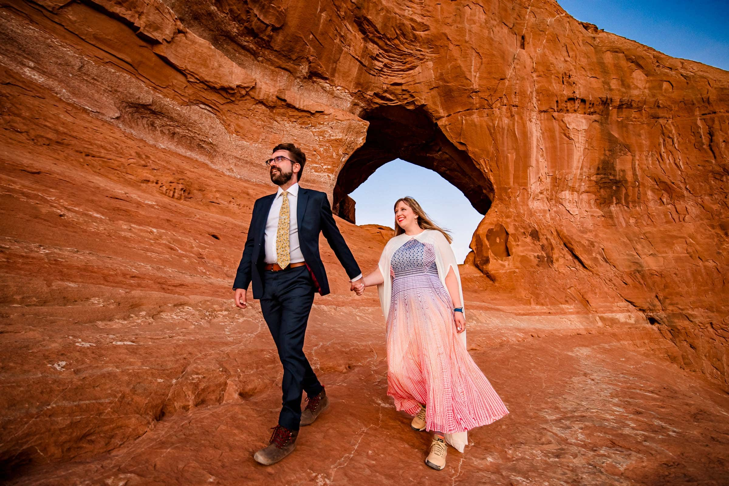 Bride and groom under walking through landscape in a red-rock wonderland in Moab Utah during their adventure elopement