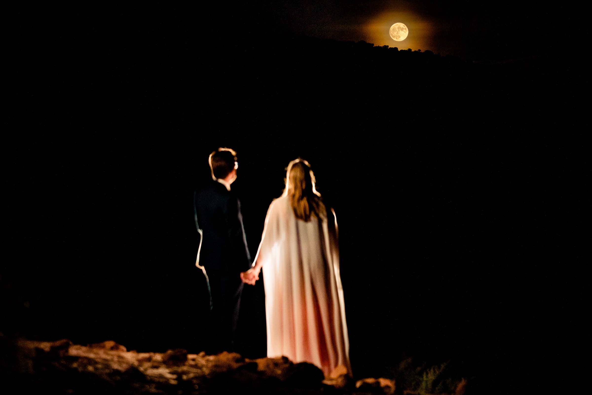 Bride and groom standing and watching the full moon in Moab Utah during their adventure elopement