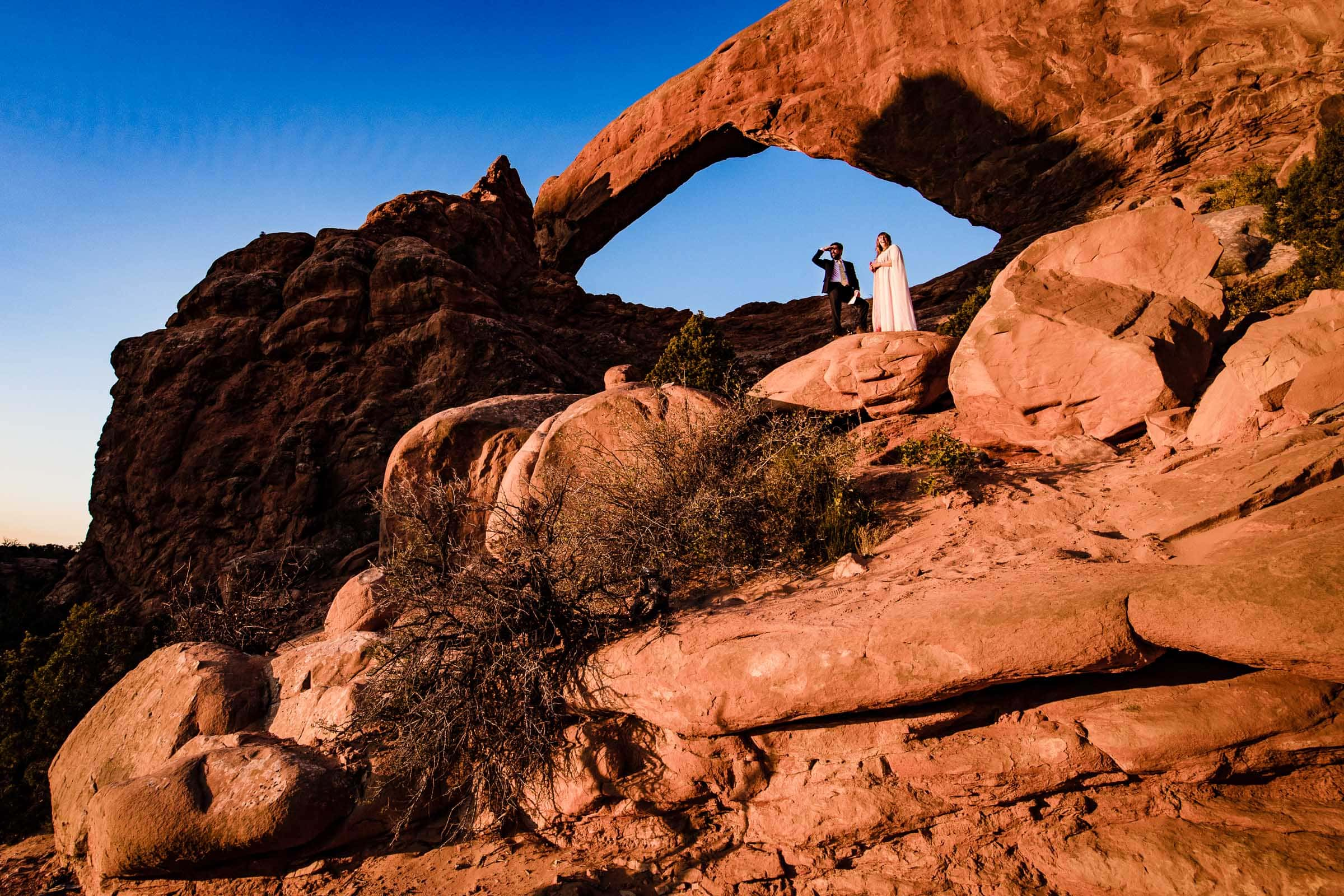 Sunrise Moab elopement ceremony with the bride and groom in the Windows Section of Arches National Park in Utah.