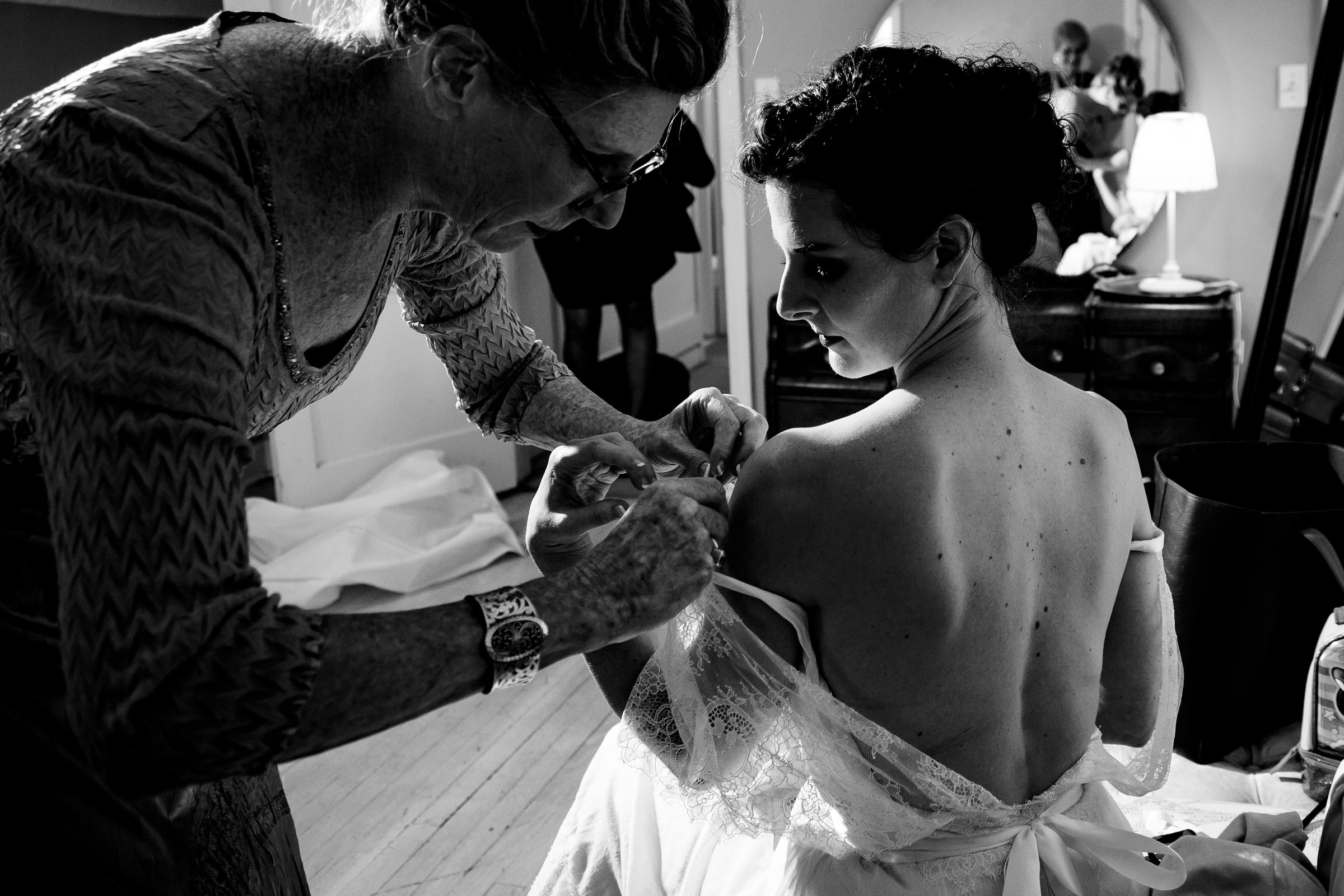 Bride getting ready for her small Kansas City elopement with her mother while putting her dress on.
