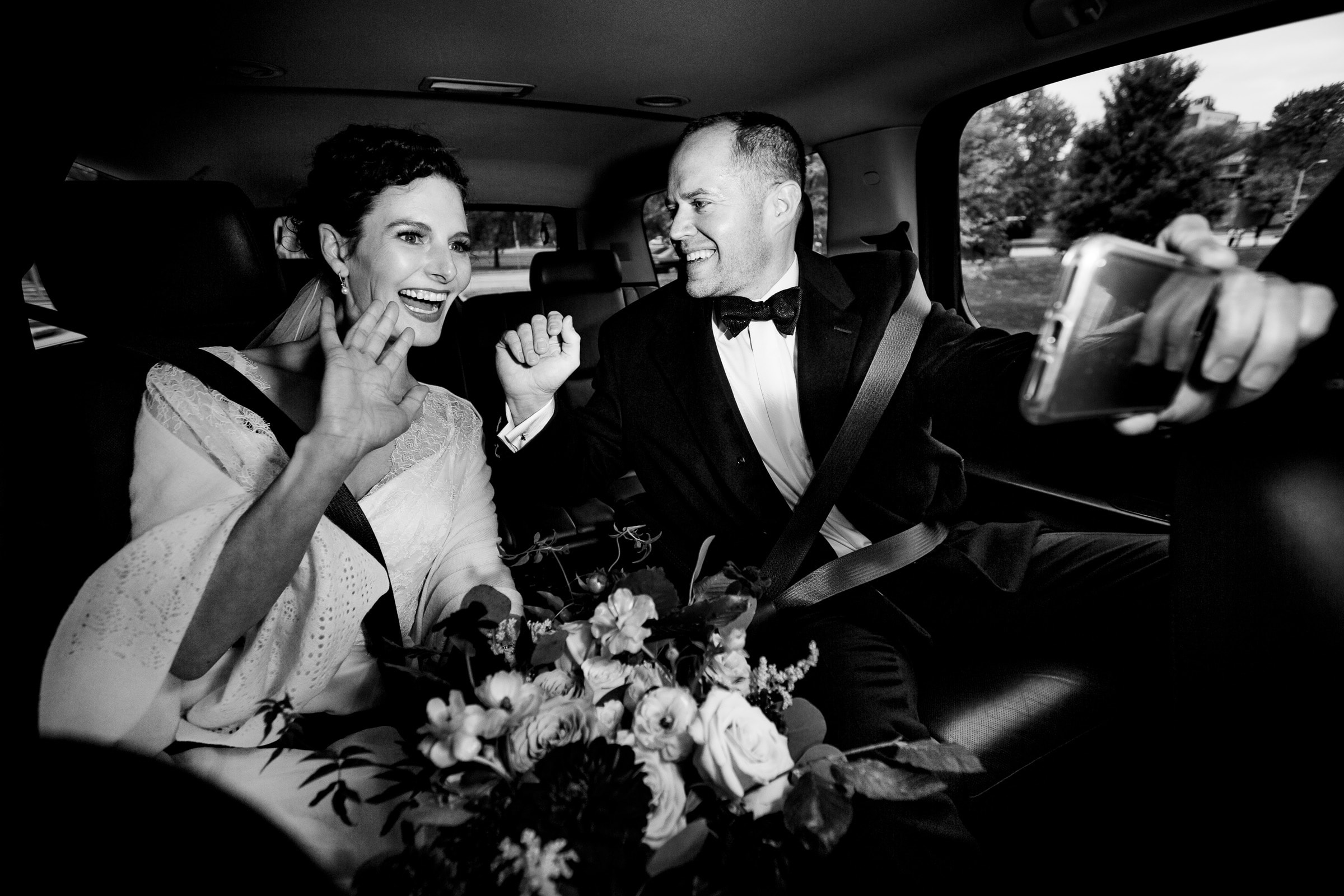 Bride and Groom celebrating to friends on an iPhone after their Kansas City wedding ceremony at the Pilgrim ChapelKansas City elopement