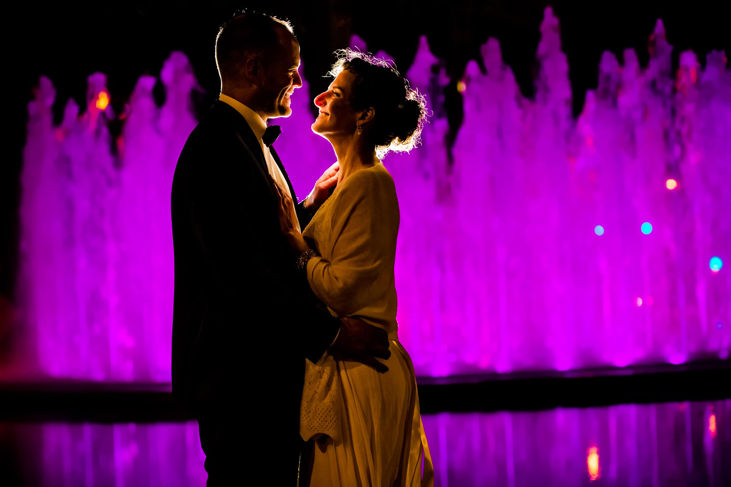 Creative bride and groom portrait near a massive water fountain during their Kansas City elopement night.
