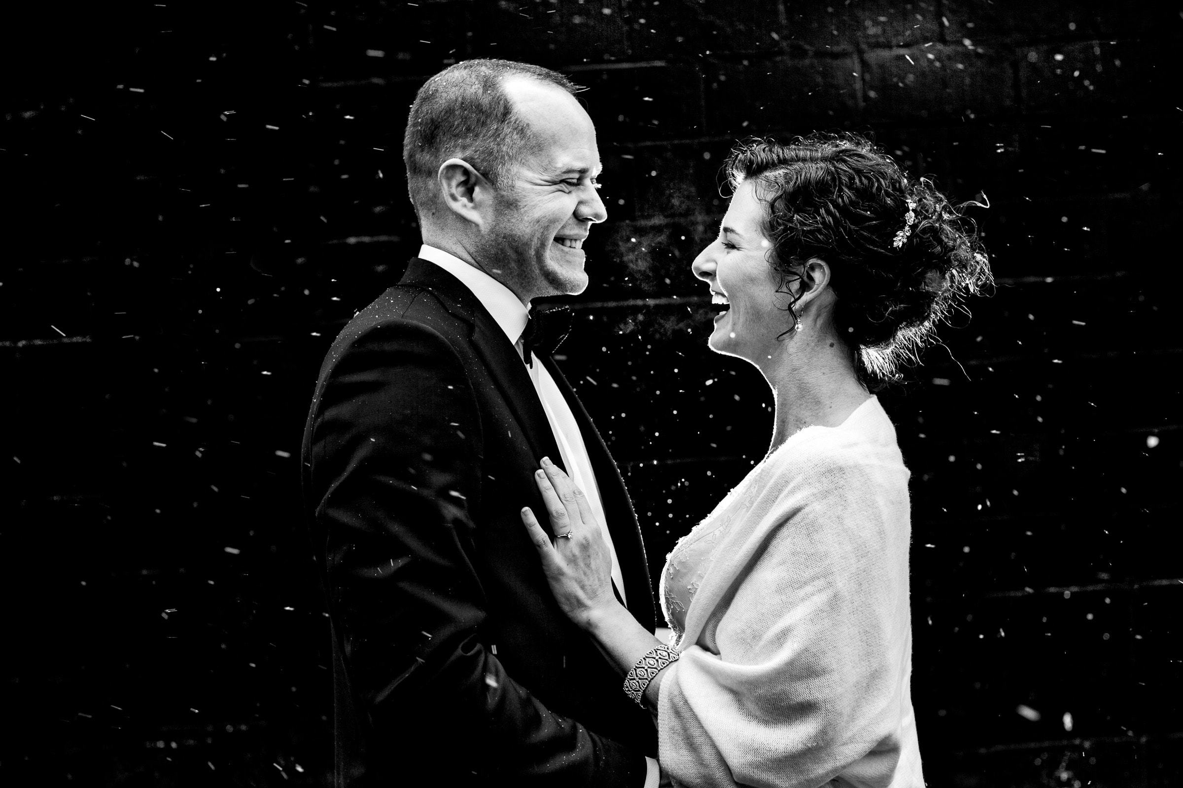 Bride and Groom laughing in the snow after their Kansas City elopement ceremony at The Pilgrim Chapel.
