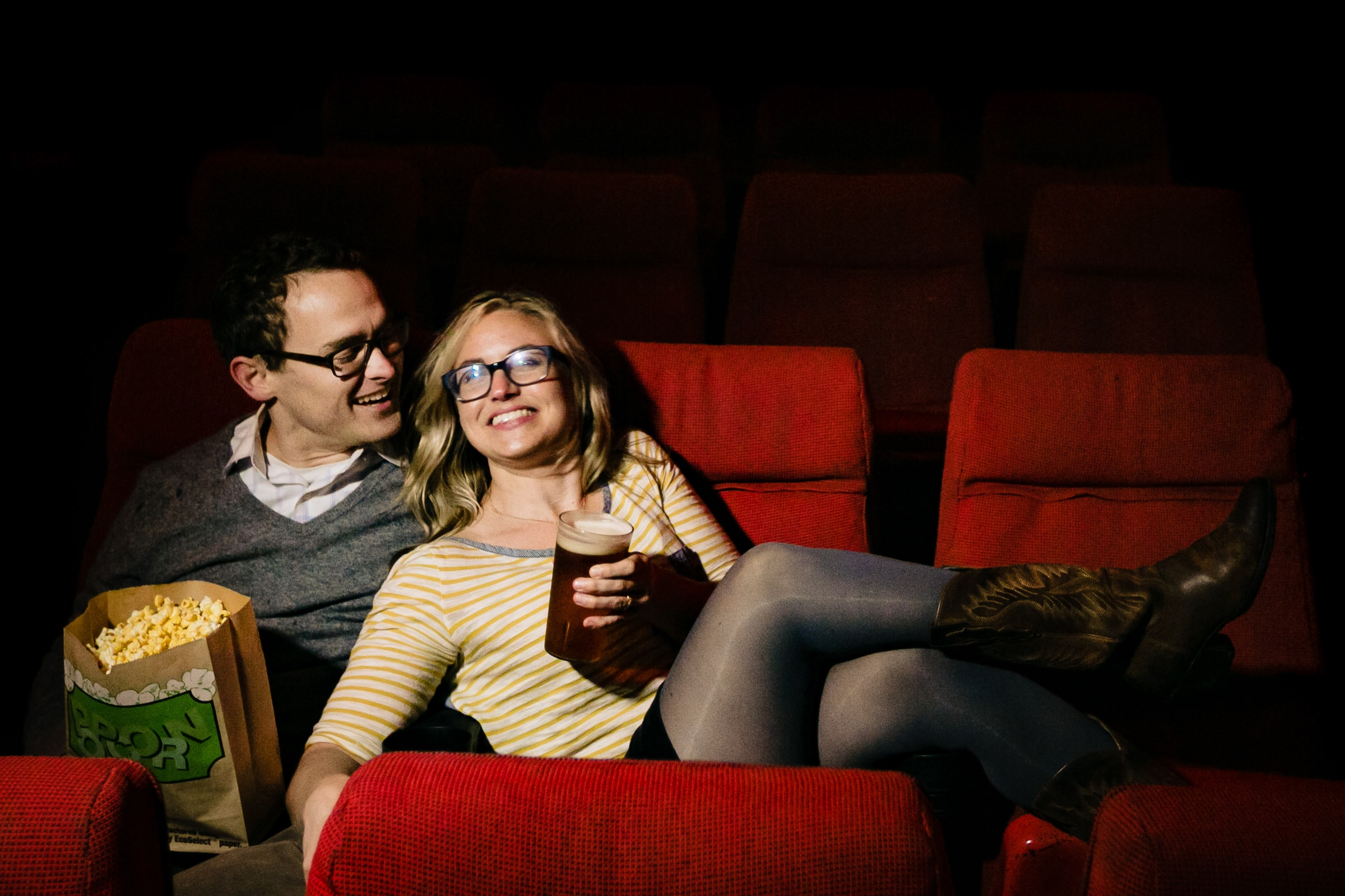 Engagement Portrait of a couple in a movie theatre eating popcorn in Portland Oregon